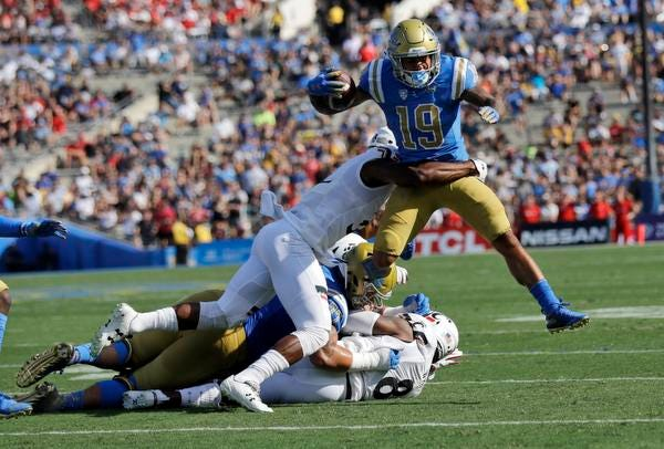 UCLA running back Kazmeir Allen (19) is tackled by Cincinnati defensive end Malik Vann during the first half of an NCAA college football game Saturday, Sept. 1, 2018, in Pasadena, Calif. (AP Photo/Marcio Jose Sanchez)