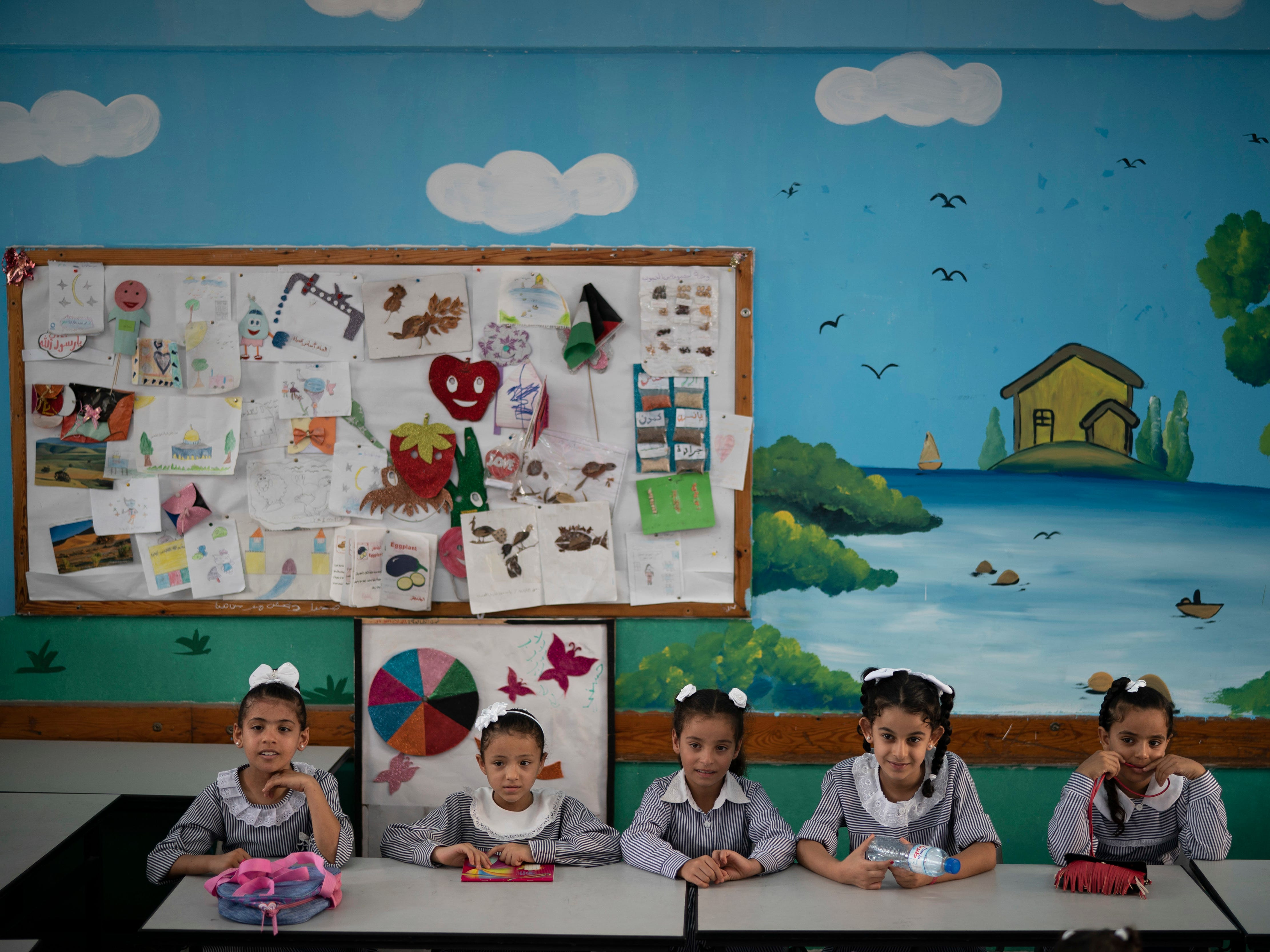 "File - In this Wednesday, Aug. 29, 2018 file photo, girls sit inside a classroom at an UNRWA school during the first day of a new school year in Gaza City. A spokesman for the Palestinian president says the American decision to cut funding for the U.N. agency aiding Palestinian refugees is ""an attack on the rights of the Palestinian people."" The U.S. supplies nearly 30 percent of the total budget of the U.N. Relief and Works Agency, or UNRWA, and had been demanding it carry out significant reforms. The decision cuts nearly $300 million of planned support. (AP Photo/Felipe Dana, File) ORG XMIT: DV101"
