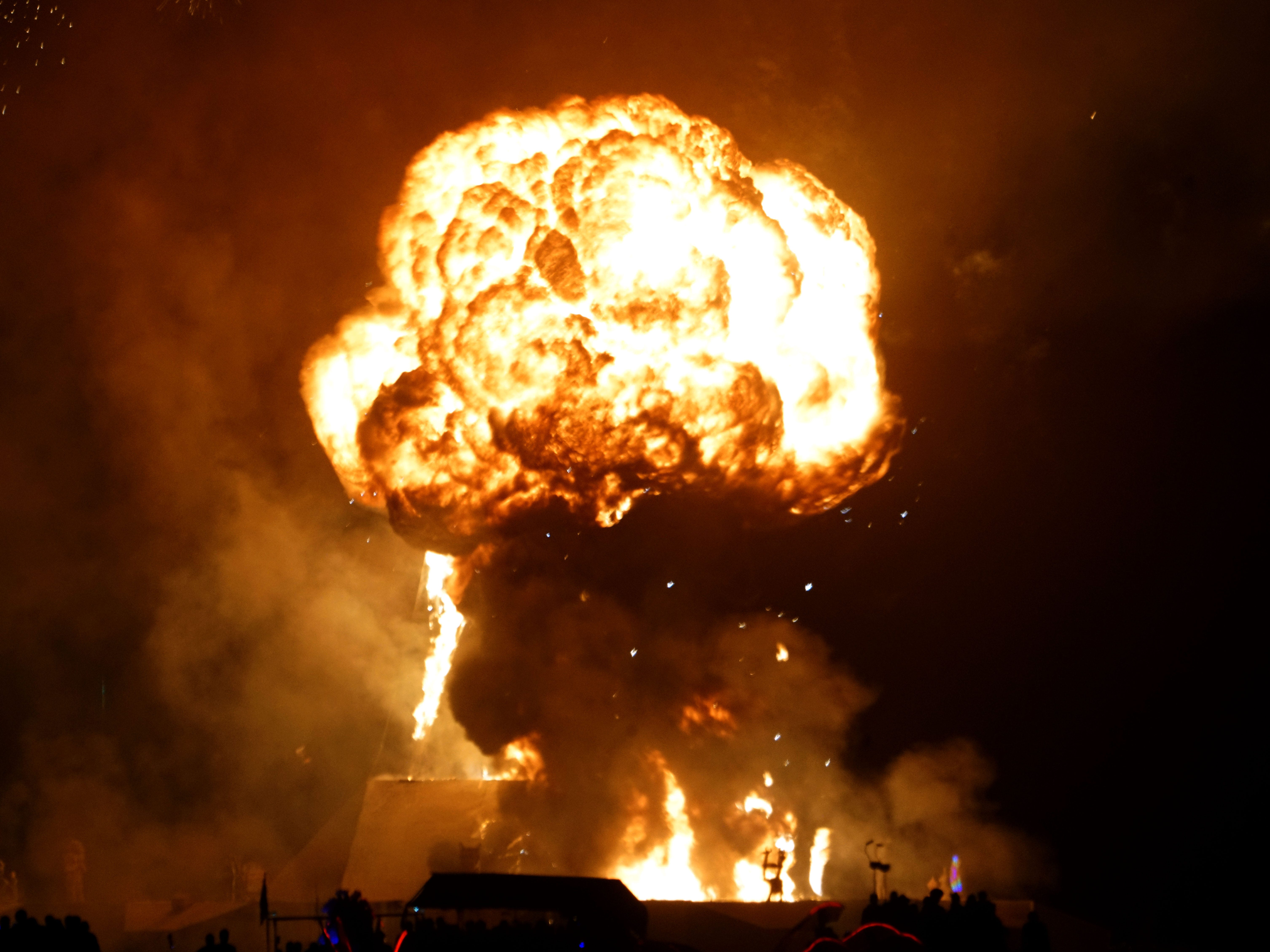 A massive explosion dwarfs the approximately 100-foot-tall Man effigy as it burns on Saturday night during a raucous celebration at Burning Man Sept. 2, 2018.