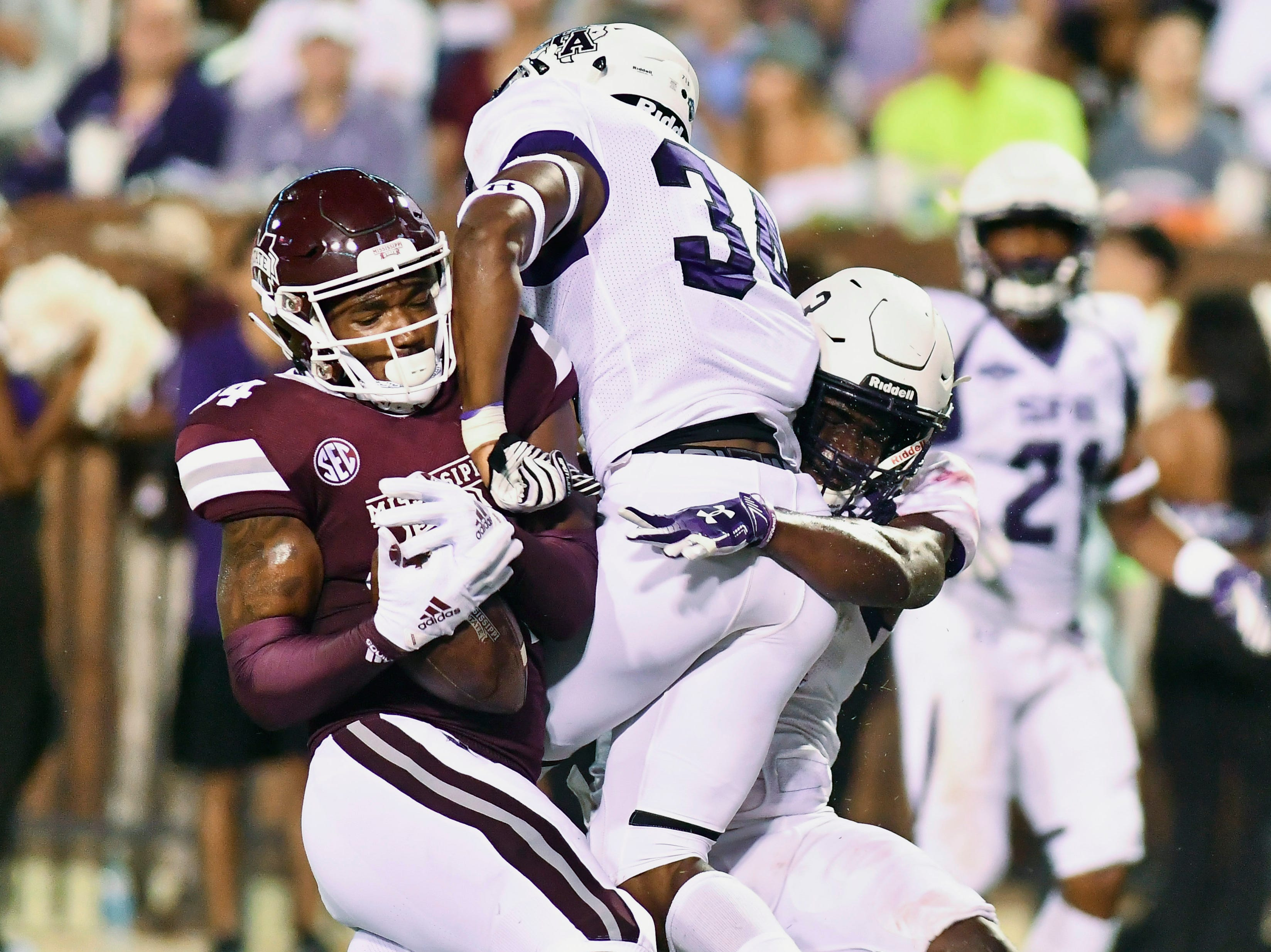 Mississippi State Bulldogs tight end Dontea Jones (84) makes a reception for a touchdown as he is defended by Stephen F. Austin Lumberjacks safety Gavin Roland (34) and safety Lawrence Ghansah (3) during the second quarter at Davis Wade Stadium.