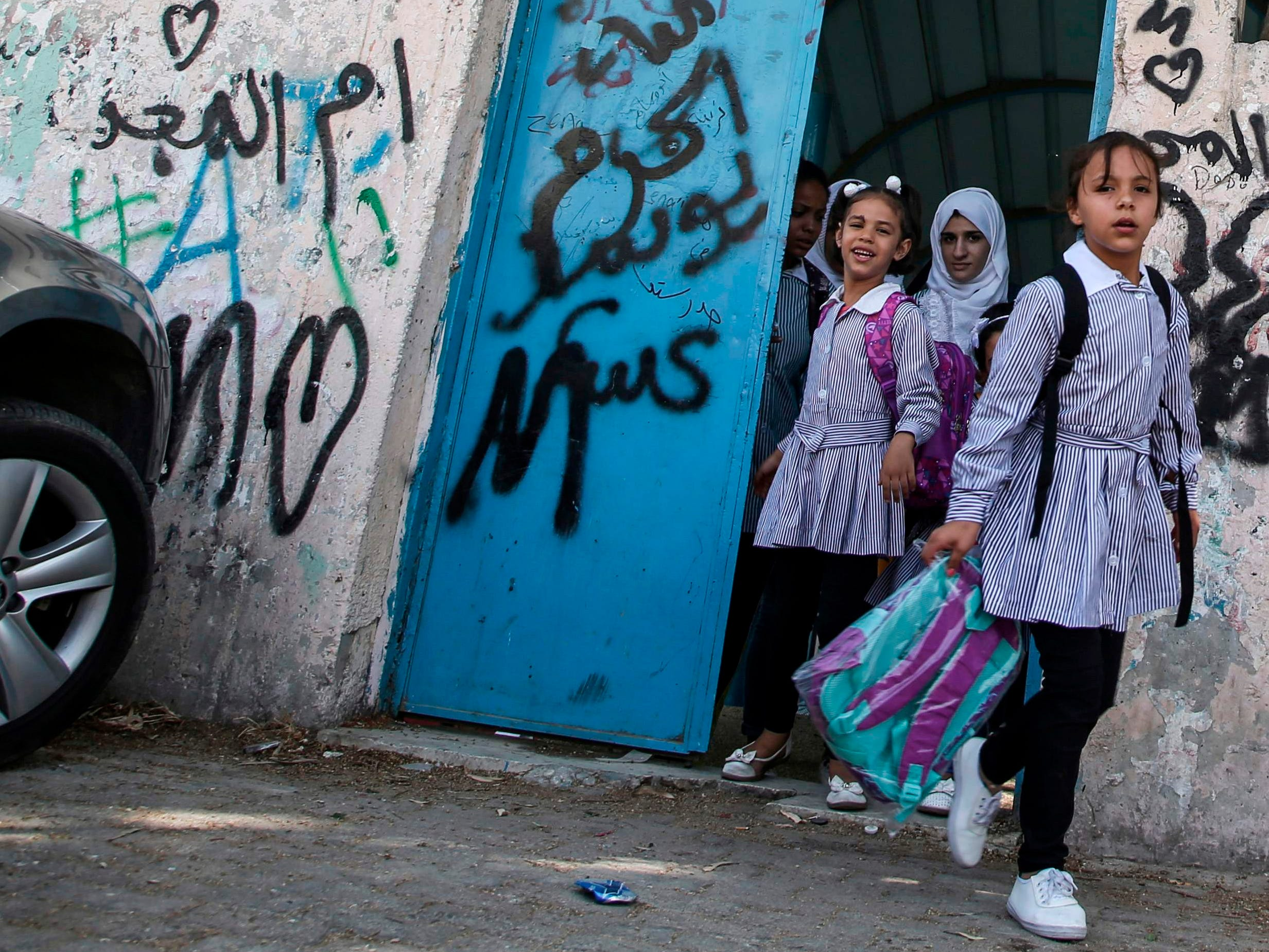 "Palestinian girls exit from a school run by the United nations Relief and Works Agency's (UNRWA, UN agency for Palestinian refugees), in the Askar refugee camp east of Nablus in the occupied West Bank on September 2, 2018. - The United States, the biggest contributor to the UNRWA -- a lifeline for millions of Palestinians for over 70 years, announced on August 31 it was halting its funding to the organisation, which it labelled ""irredeemably flawed"". (Photo by Jaafar ASHTIYEH / AFP)JAAFAR ASHTIYEH/AFP/Getty Images ORIG FILE ID: AFP_18S6VS"