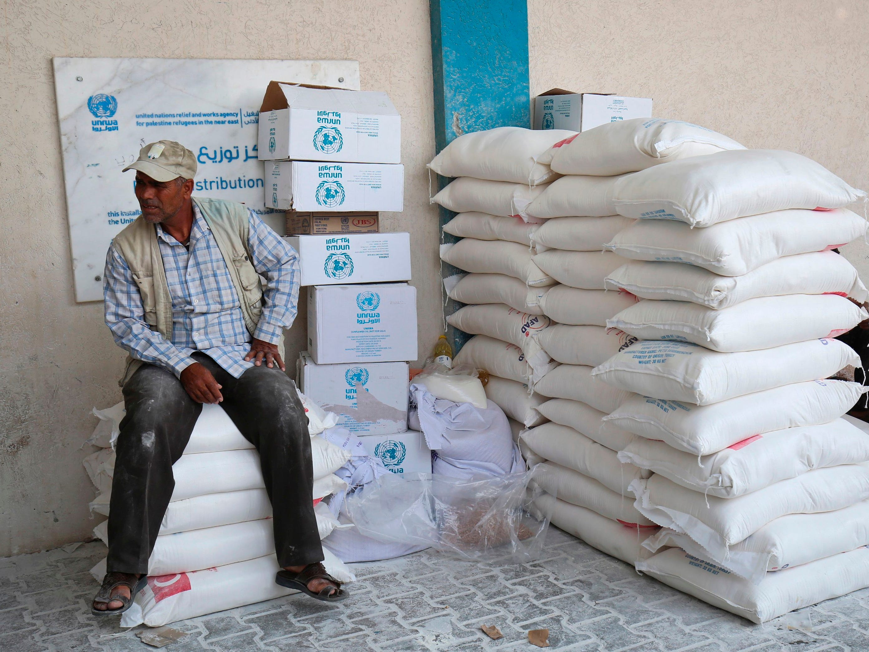 "A Palestinian man sits by sacks of flour inside an United Nations' compound after receiving food supplies at the Rafah refugee camp in the southern Gaza Strip on September 1, 2018. - The United States announced it was halting funding for the United Nations' agency for Palestinian refugees after declaring the organisation was ""irredeemably flawed. Washington has long been the UN Relief and Works Agency's (UNRWA) largest donor but is ""no longer willing to shoulder the very disproportionate share of the burden,"" State Department spokeswoman Heather Nauert said in a statement. (Photo by SAID KHATIB / AFP)SAID KHATIB/AFP/Getty Images ORG XMIT: 187 ORIG FILE ID: AFP_18R7CL"