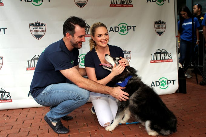 Houston Astros starting pitcher Justin Verlander and wife Kate Upton pose for photos with a dog up for adoption during the Astros' Dog Day event.