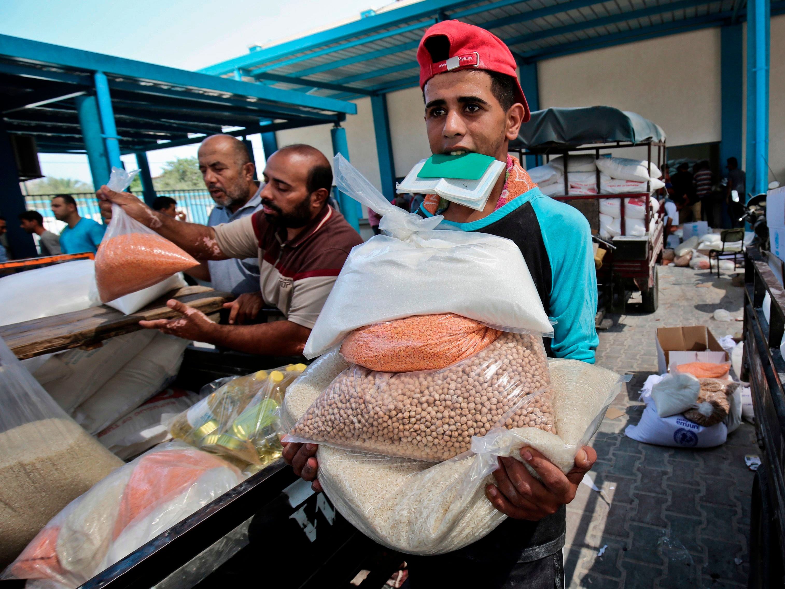 "Palestinian men collect aid food at a United Nations' compound in the Rafah refugee camp in the southern Gaza Strip on September 1, 2018. - The United States announced it was halting funding for the United Nations' agency for Palestinian refugees after declaring the organisation was ""irredeemably flawed. Washington has long been the UN Relief and Works Agency's (UNRWA) largest donor but is ""no longer willing to shoulder the very disproportionate share of the burden,"" State Department spokeswoman Heather Nauert said in a statement. (Photo by SAID KHATIB / AFP)SAID KHATIB/AFP/Getty Images ORG XMIT: 200 ORIG FILE ID: AFP_18R7ND"