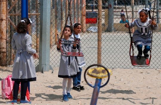 """Palestinian schoolgirls play at the U.N. Relief and Works Agency's (UNRWA) school in the Rafah refugee camp, southern Gaza Strip, on Sept. 1.  The United States announced it was halting funding for the United Nations' agency for Palestinian refugees after declaring the organization was """"irredeemably flawed."""""""