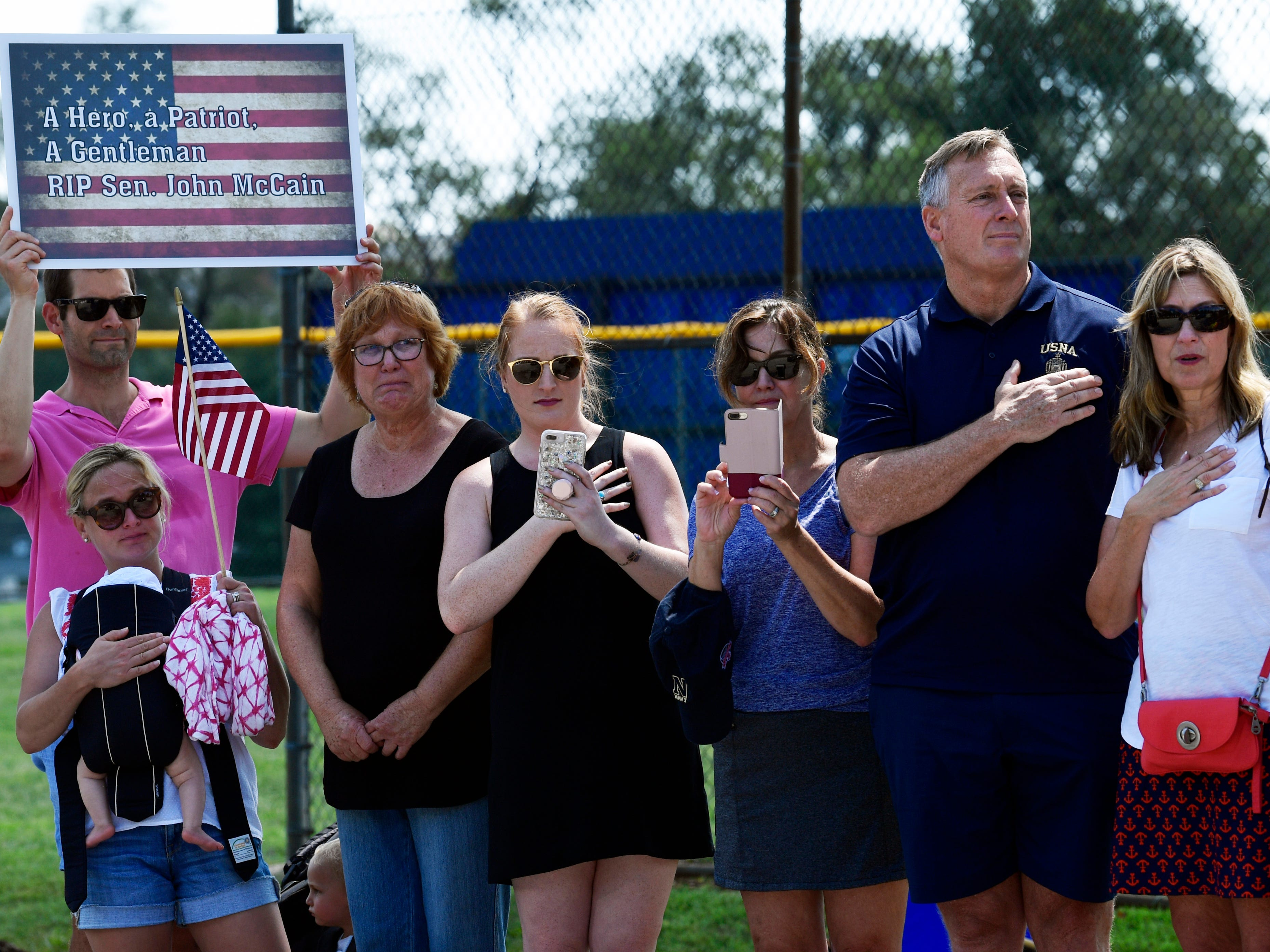 People watch as the funeral procession for Sen. John McCain, R-Ariz., arrives at the United States Naval Academy in Annapolis, Md., Sunday, Sept. 2, 2018, for his funeral service and burial. McCain died Aug. 25 from brain cancer at age 81. (AP Photo/Susan Walsh) ORG XMIT: MDSW102