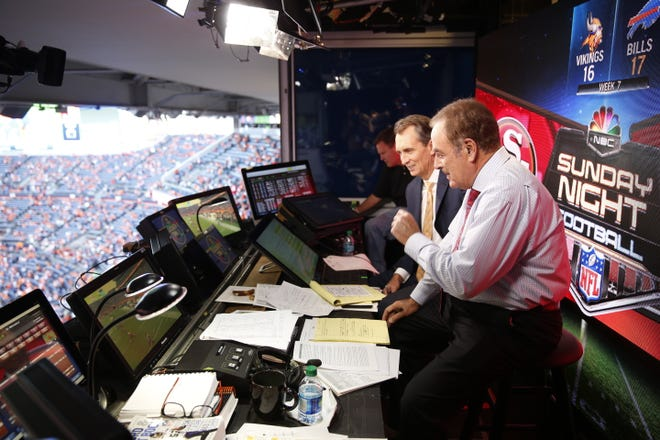 "In a file photo from 2014, Al Michaels (right) and Cris Collinsworth (center) in the broadcast booth before a game on ""Sunday Night Football."""