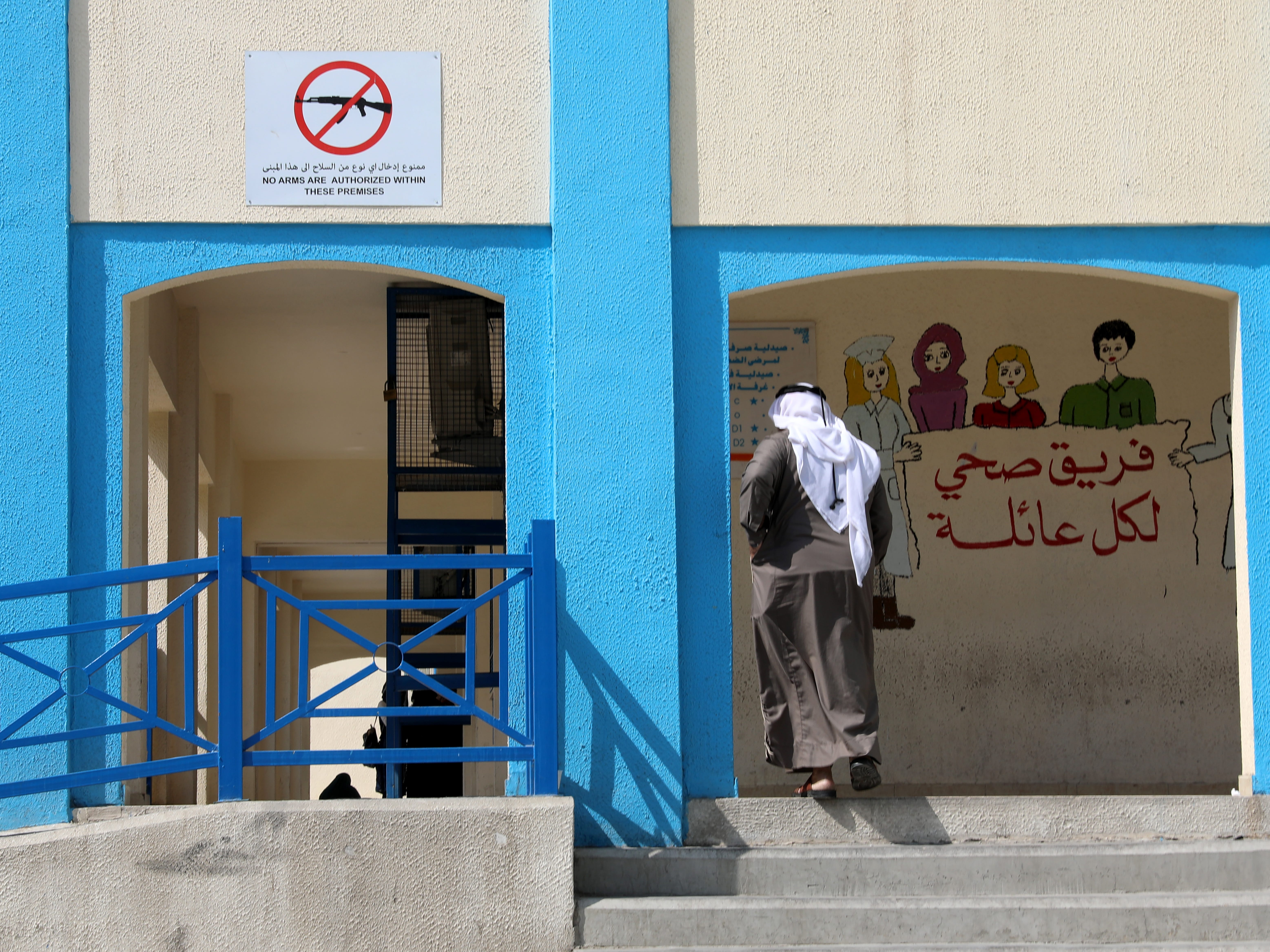 A Palestinian refugee in Jordan walks past a 'no weapons allowed' sign outside a clinic of the United Nations Relief and Works Agency for Palestine Refugees in the Near East (UNRWA), at the new Amman camp on the outskirts of Amman, Jordan on Sept. 2, 2018.