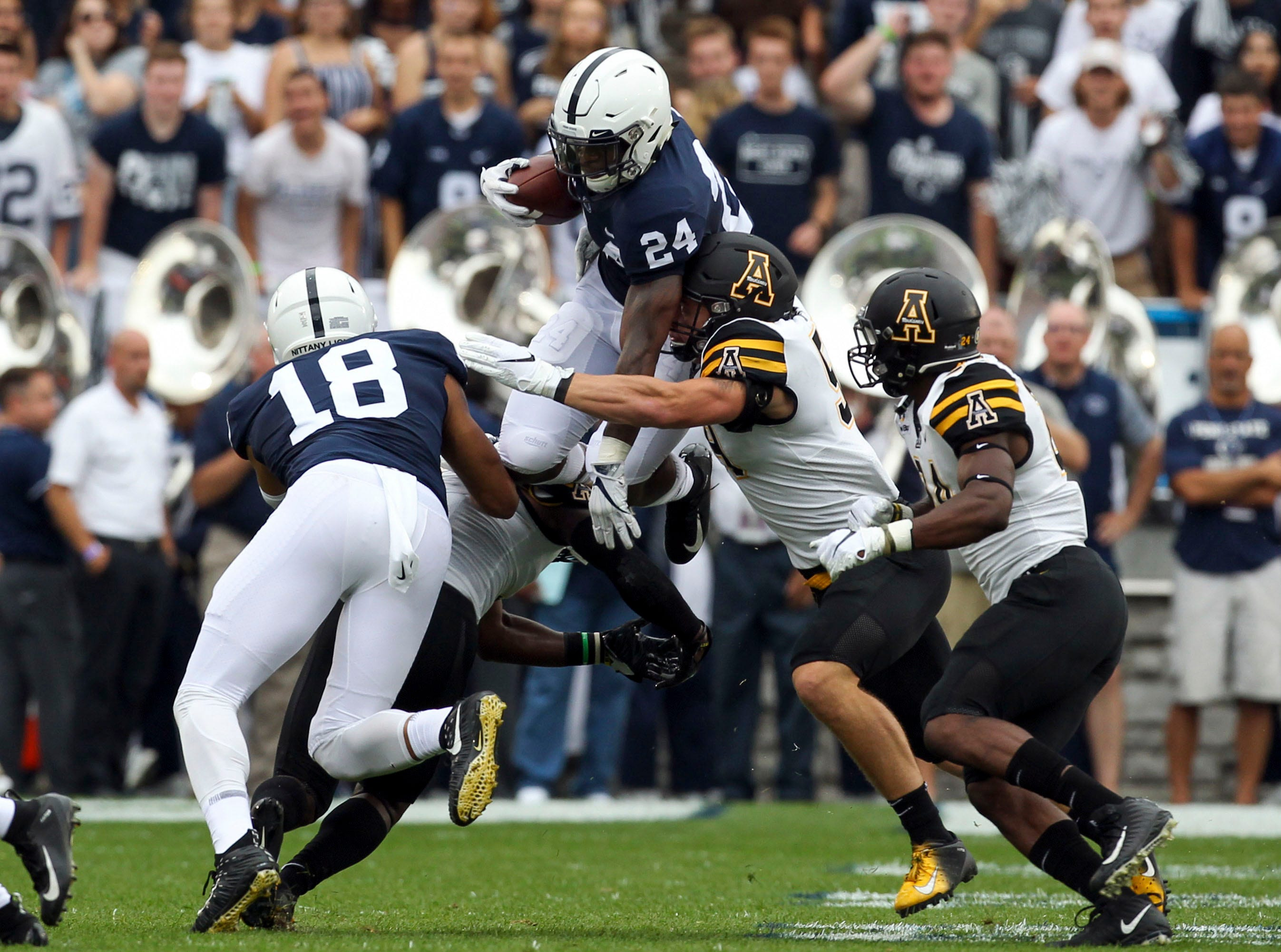 Penn State Nittany Lions running back Miles Sanders (24) jumps over a defender during the first quarter against the Appalachian State Mountaineers at Beaver Stadium.