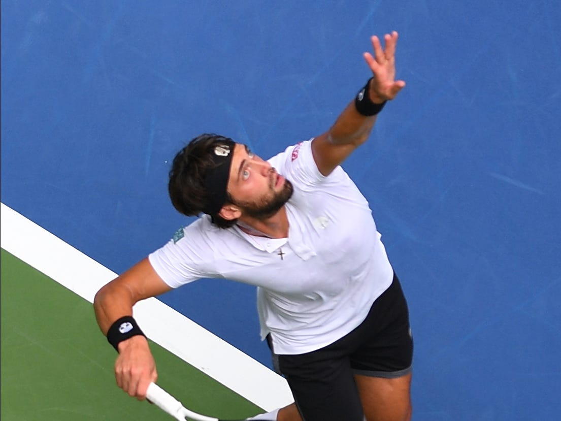 Nikoloz Basilashvili of Georgia serves to Rafael Nadal of Spain.