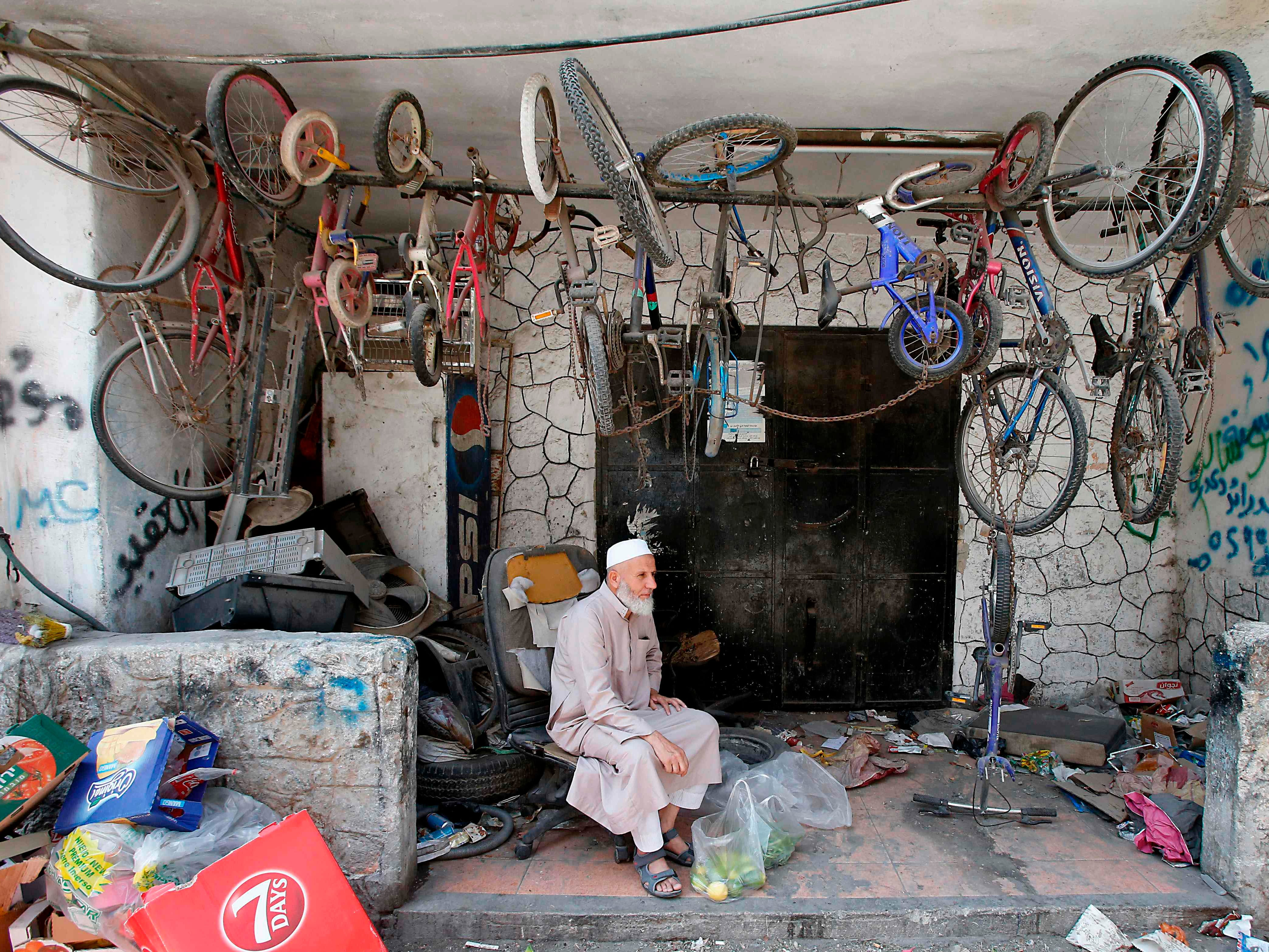 "A Palestinian man sits by bicycles at the United nations Relief and Works Agency's (UNRWA, UN agency for Palestinian refugees) Fawwar Palestinian refugee camp, southern West Bank, near Hebron, on September 2, 2018. - The UN agency for Palestinian refugees (UNRWA) has been a lifeline for millions of Palestinians since it was set up nearly 70 years ago. On August 31, the United States, by far the biggest contributor to the agency, announced it was halting its funding to the organisation, which it labelled ""irredeemably flawed"". The Naqba, ""Day of Catastrophe"" refers to the day, 15 May 1948, when the modern state of Israel was established following the Arab-Israeli war, which led to the displacement of the Palestinian people. (Photo by HAZEM BADER / AFP)HAZEM BADER/AFP/Getty Images ORIG FILE ID: AFP_18S6JT"