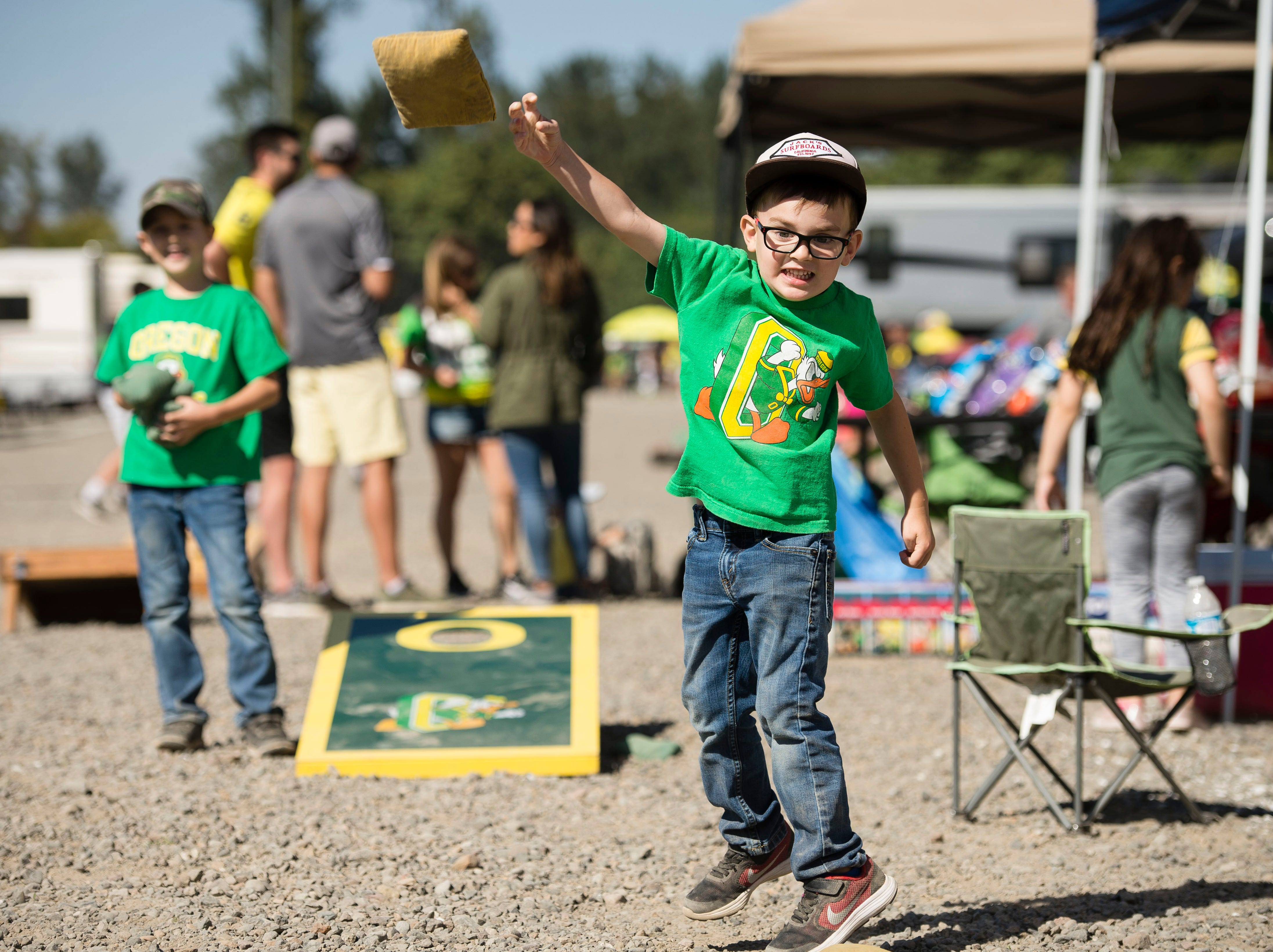 Cash Schimmer, 4, of Eugene, Oregon, plays a game of cornhole with his family before the start of a game between the Oregon Ducks and Bowling Green Flacons at Autzen Stadium.