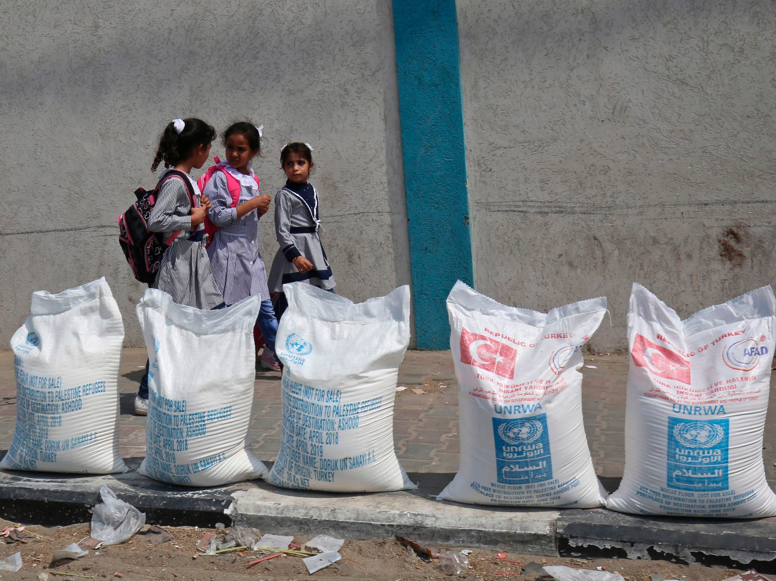 "Palestinian school girls walk past sacks of flour outside a United Nations' compound at the Rafah refugee camp in the southern Gaza Strip on September 1, 2018. - The United States announced it was halting funding for the United Nations' agency for Palestinian refugees after declaring the organisation was ""irredeemably flawed. Washington has long been the UN Relief and Works Agency's (UNRWA) largest donor but is ""no longer willing to shoulder the very disproportionate share of the burden,"" State Department spokeswoman Heather Nauert said in a statement. (Photo by SAID KHATIB / AFP)SAID KHATIB/AFP/Getty Images ORG XMIT: 190 ORIG FILE ID: AFP_18R7CP"