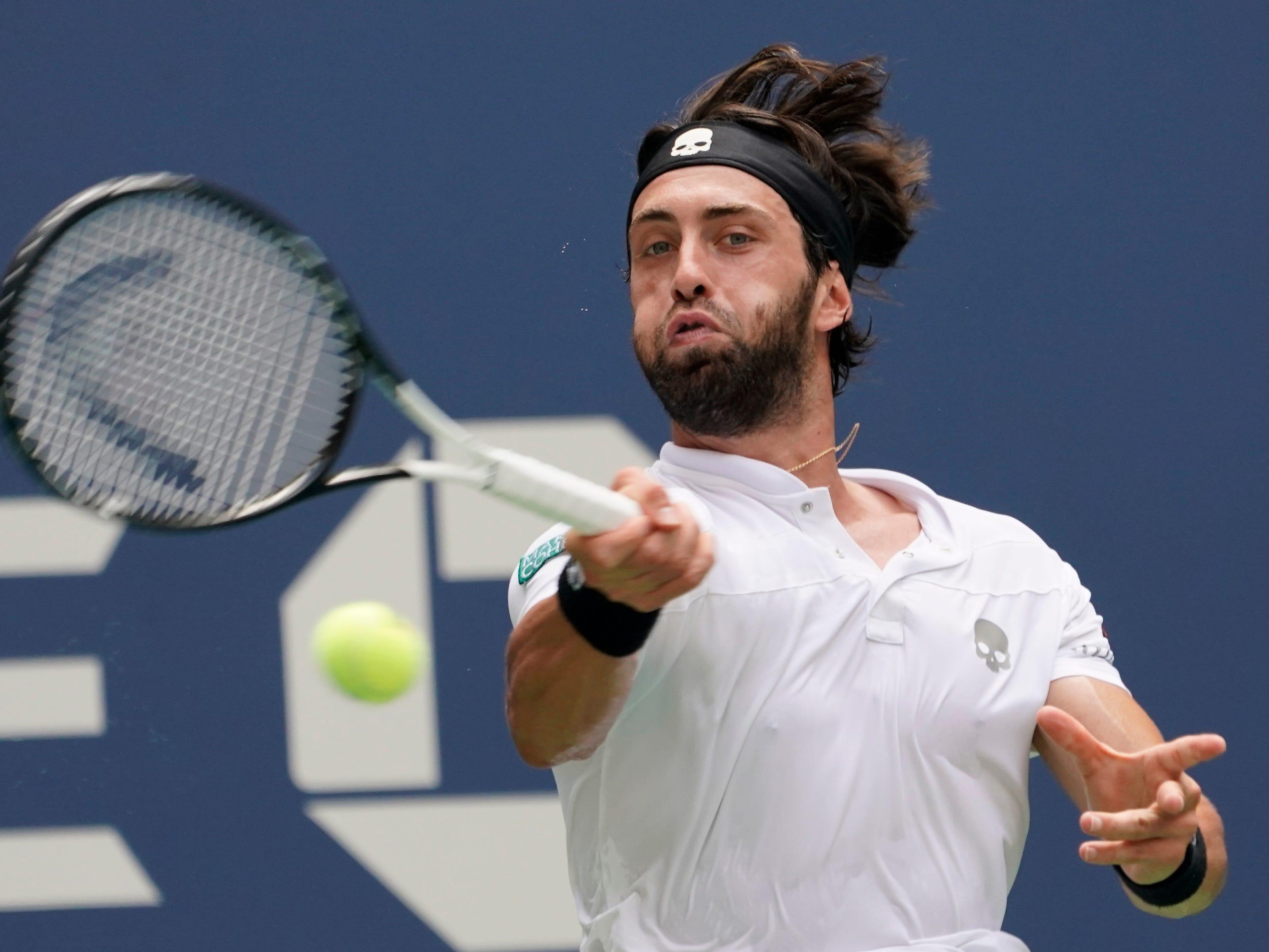 Nikoloz Basilashvili hits to Rafael Nadal.