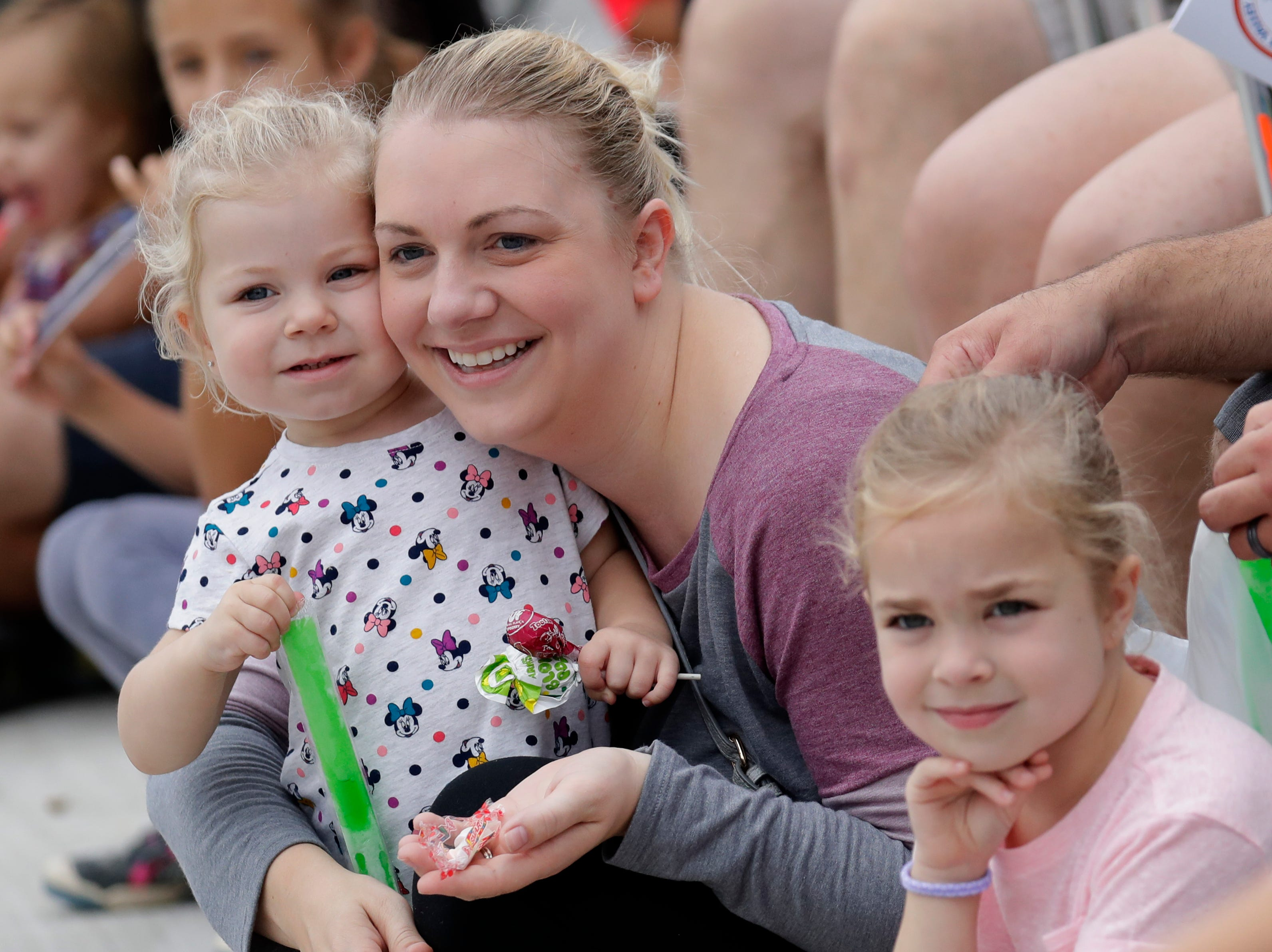 Ashley Landskrom of Greenville and her daughters Olivia, 2, left, and Emma, 5, right, enjoy the Neenah-Menasha Labor Day Parade Monday, Sept. 3, 2018, in downtown Menasha, Wis. 