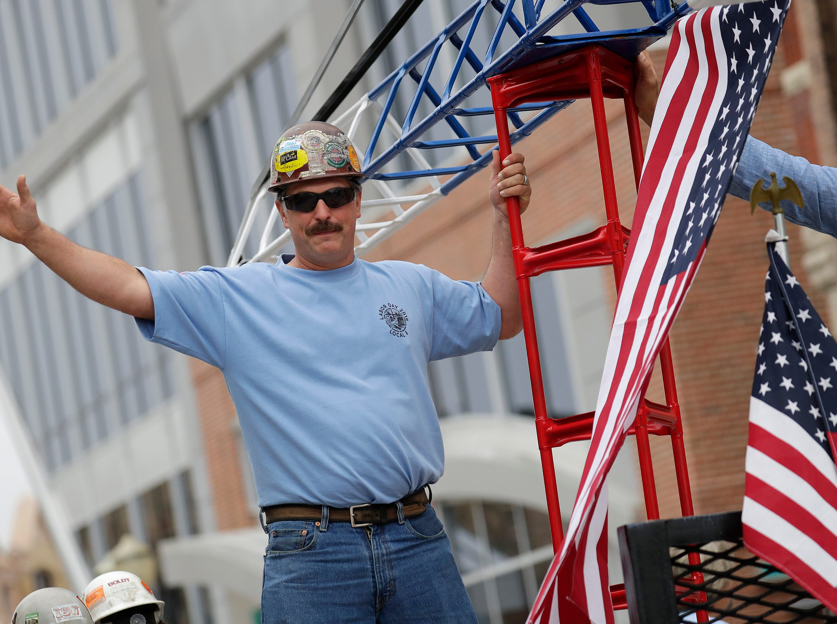 Brad Peterson Sr. of New London, a member of Ironworkers Local 8, waves to attendees during the Neenah-Menasha Labor Day Parade Monday, Sept. 3, 2018, in downtown Menasha, Wis. 