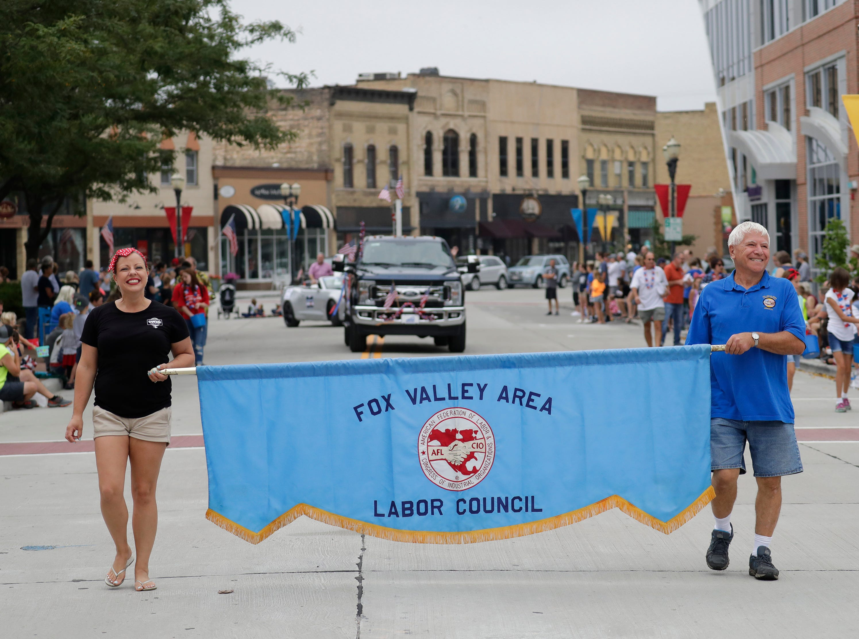 Jessica Schiessl, left, of Kimberly and Tom Brantmeier of Kaukauna participate in the Neenah-Menasha Labor Day Parade Monday, Sept. 3, 2018, in downtown Menasha, Wis. 