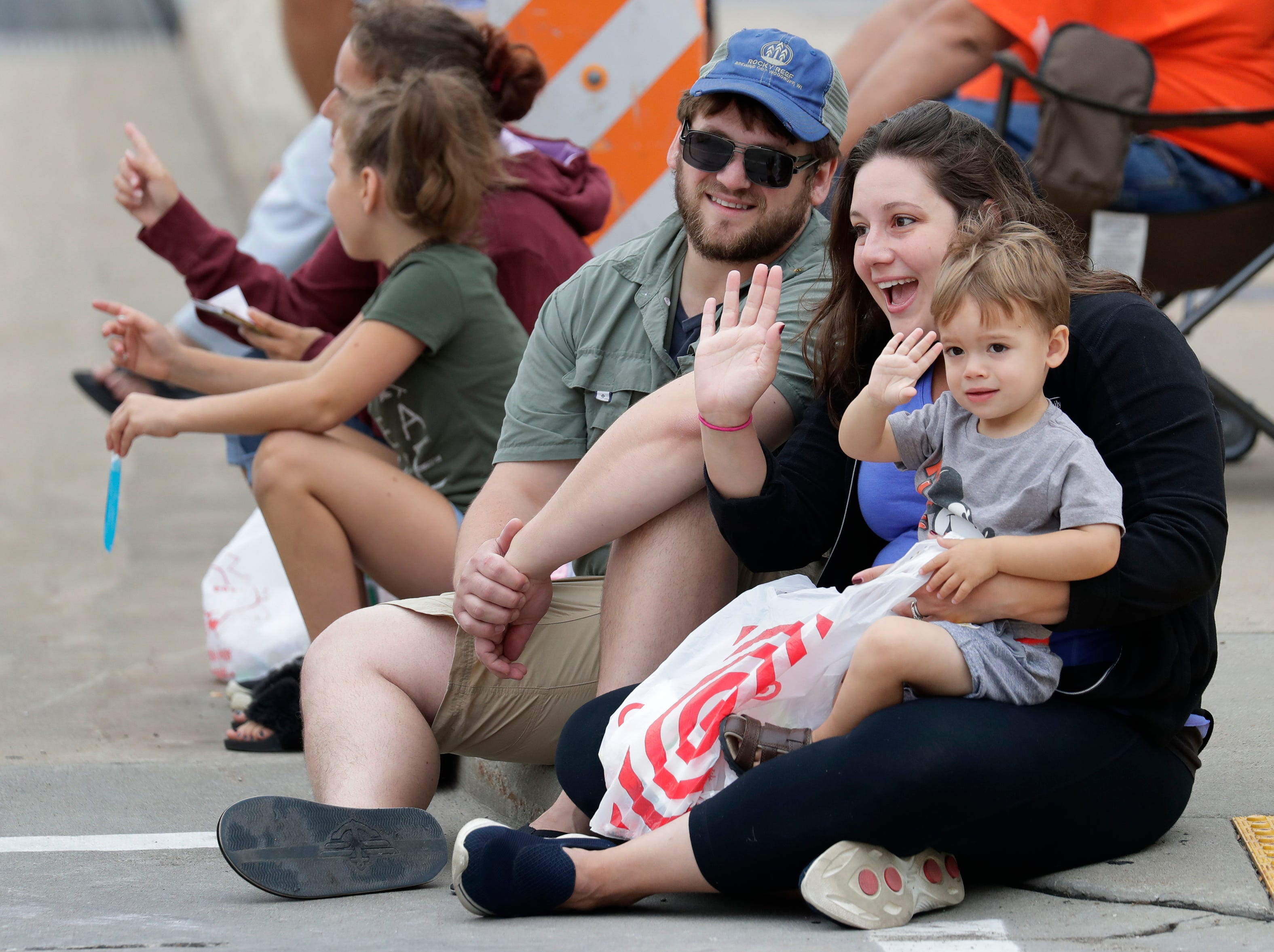 Jenny Szmanda of Menasha waves with her son David, 2, as participants pass by during the Neenah-Menasha Labor Day Parade Monday, Sept. 3, 2018, in downtown Menasha, Wis. At left is David's father Willie Szmanda.