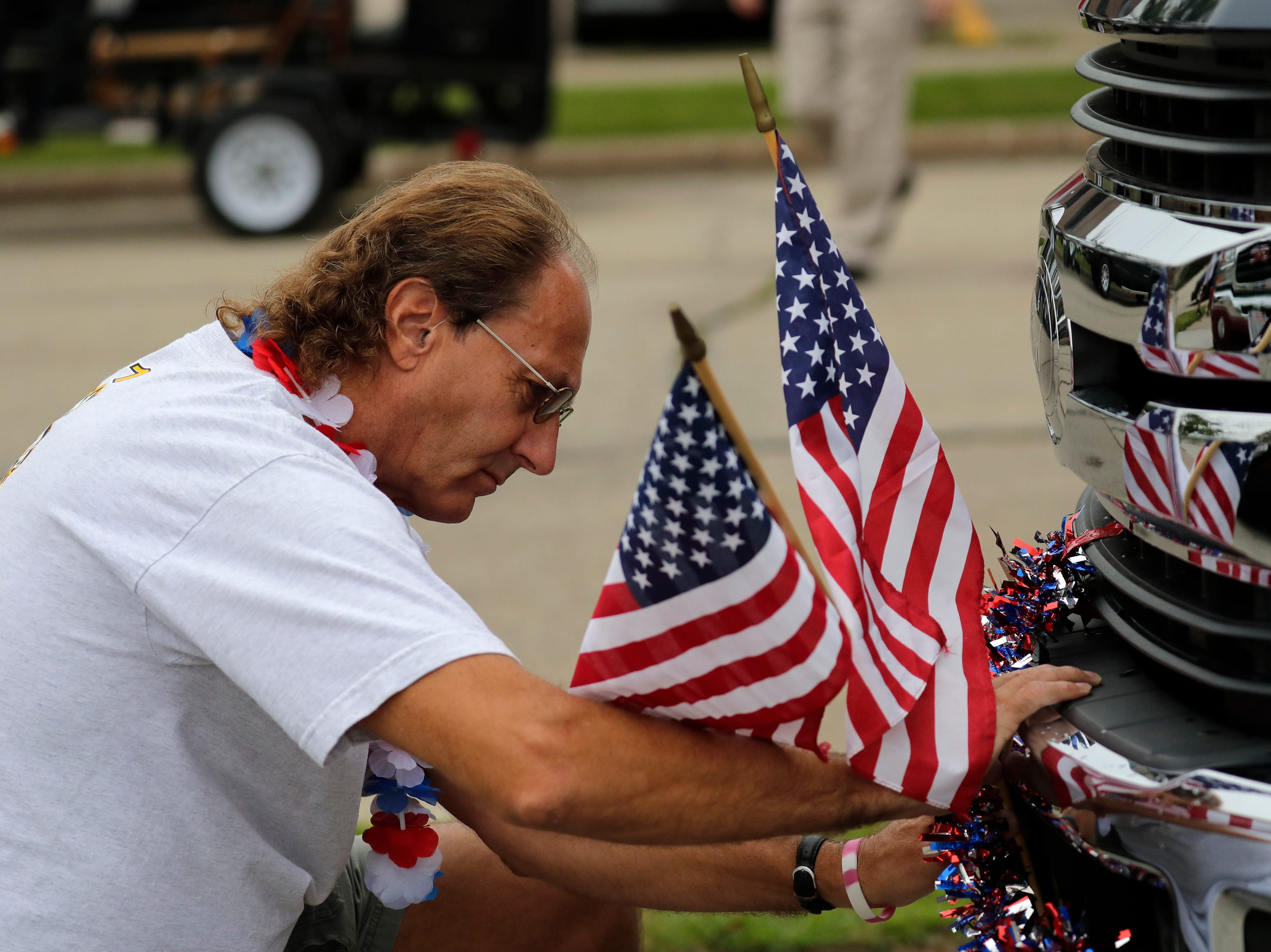 Rick Grissom of Neenah places flags on a parade vehickle prior to the start of the Neenah-Menasha Labor Day Parade Monday, Sept. 3, 2018, in downtown Menasha, Wis. 