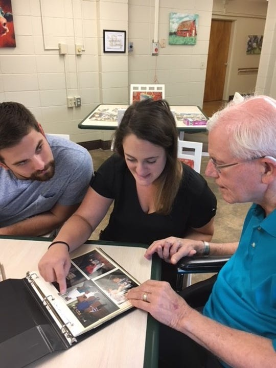 Rachel Adams and her husband, Colby Adams, look through a photo album with DeLyle Spindt Henschel Sunday at Bethany Homes in Waupaca. His bone marrow donation 25 years ago saved Rachel's life.
