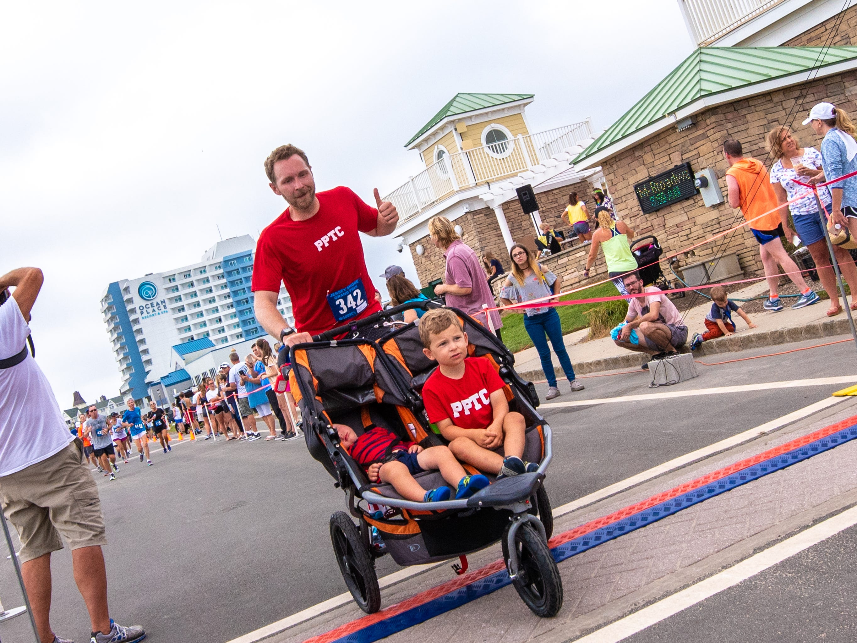 Ed Filusch, Brooklyn, NY, finishes the race while pushing a double carriage occupied by sons Luke, (left, 18 months) who slept through the whole thing and Teddy, 3. The Pier House 5K run was held along the ocean in the north end of Long Branch on Monday, September 3, 2018.  / Russ DeSantis for the Asbury Park Press