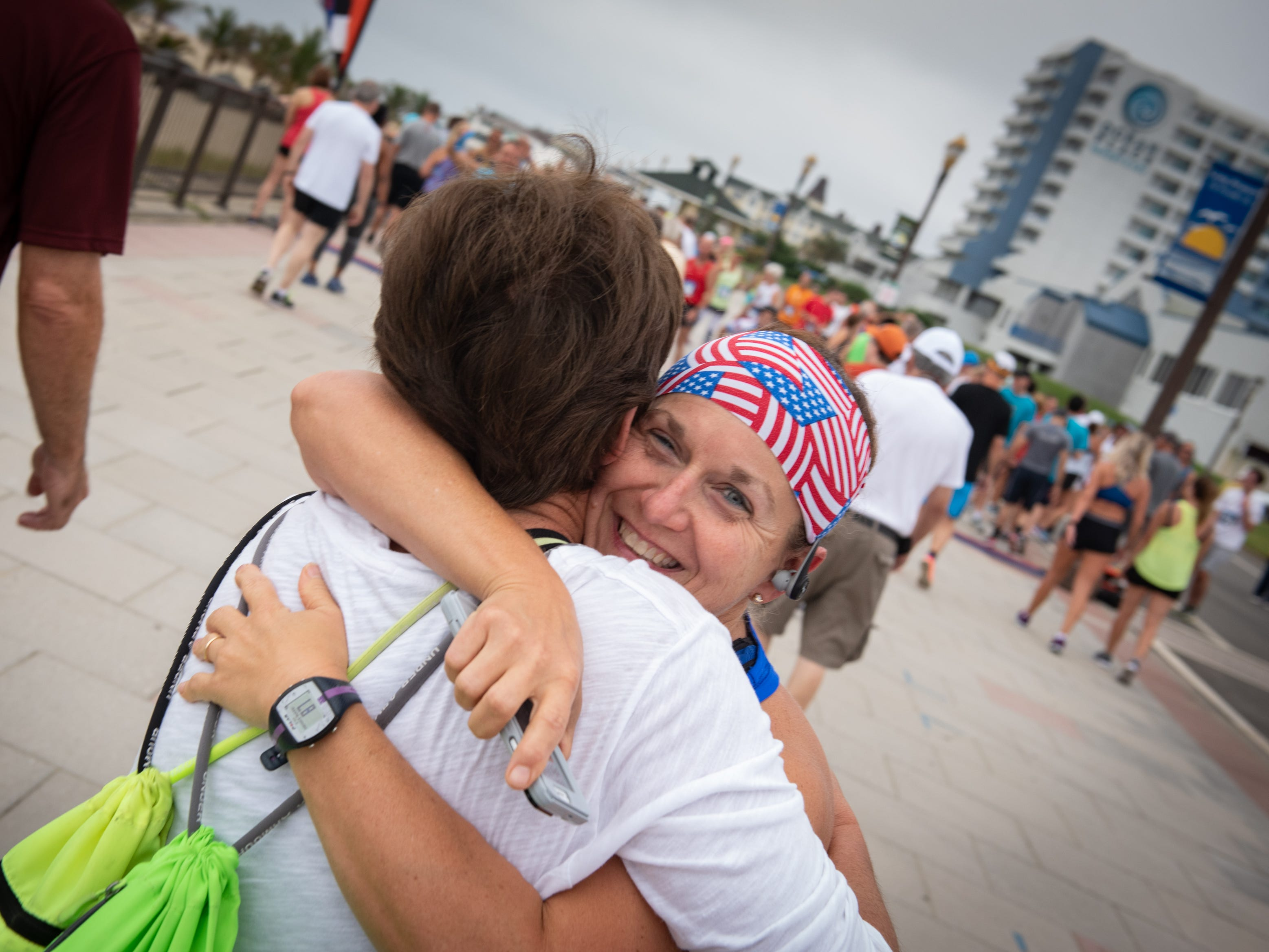 The Pier House 5K run was held along the ocean in the north end of Long Branch on Monday, September 3, 2018.  Beth Hall, (left) Beachwood, could not enter the race because of an injury but she gets a hug from her usual race partner Suzanne Burns (facing camera) of Toms River. / Russ DeSantis for the Asbury Park Press