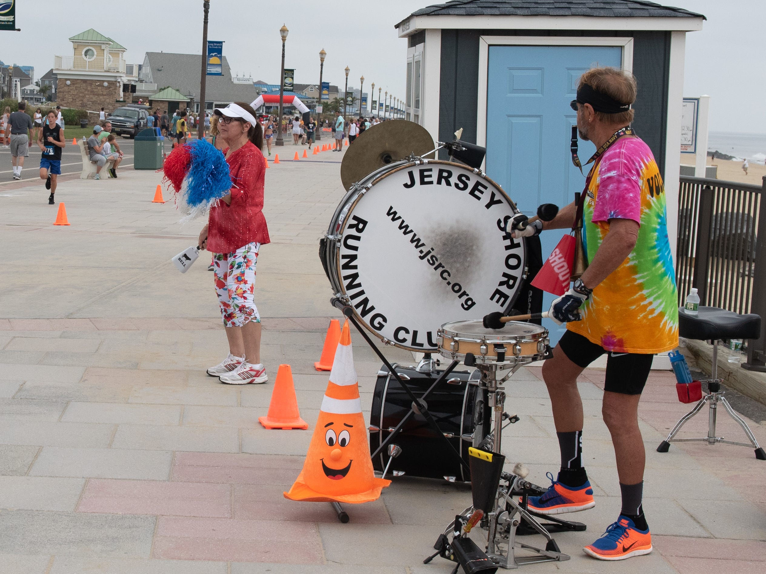 Chick (left) and Barbara Albers who act as musical cheerleaders for the runners. At left is the eventual women's winner Jamie Reuter, Leonardo, who finished at 18:08.6. The Pier House 5K run was held along the ocean in the north end of Long Branch on Monday, September 3, 2018.  / Russ DeSantis for the Asbury Park Press