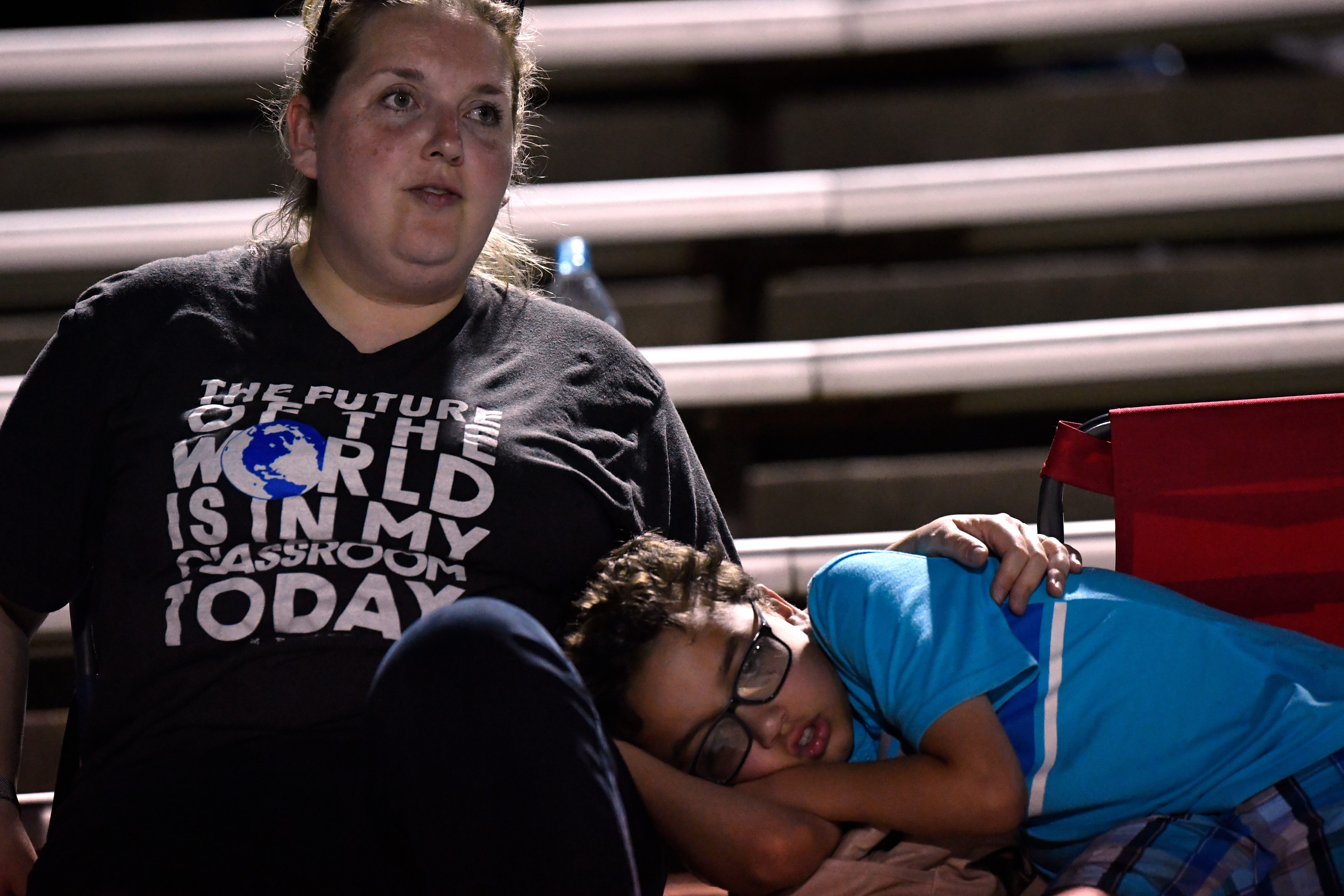 Anwar Simmons, 8, dozes next to his mother Cynthia while watching Friday's season opener for Cooper High School.