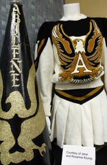 """A vintage Abilene High cheerleading outfit and megaphone are displayed at the Abilene Public Library. Local residents and organizations loaned cherished items to the """"Hometown Teams"""" exhibit, here through Oct.  6."""