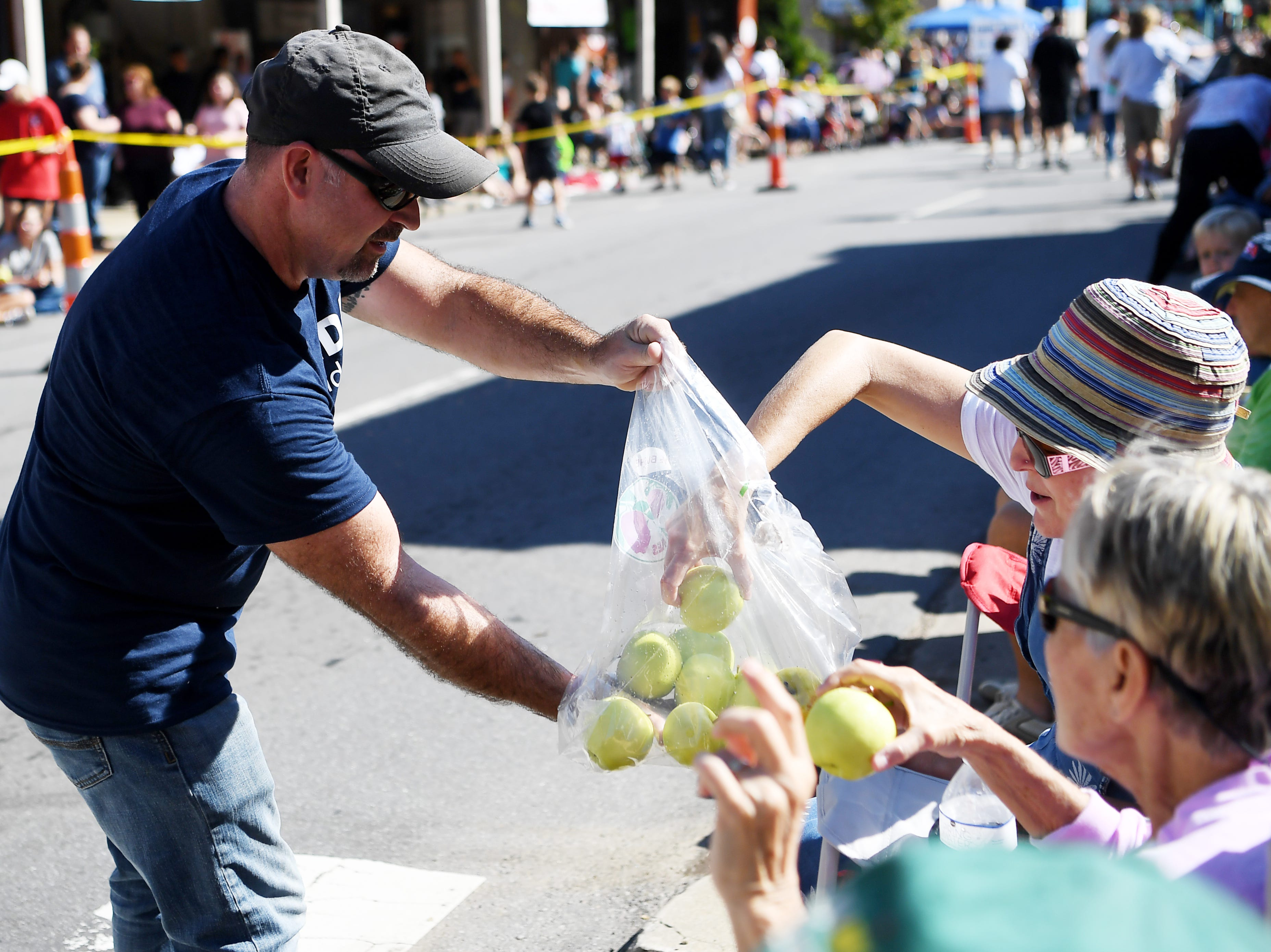 Apples are handed out to spectators during Canton's Labor Day parade September 3, 2018.