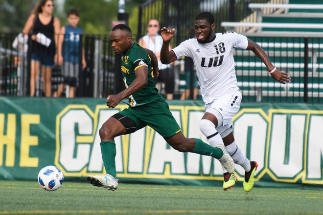Vermont's Mikel Kabala (12) runs down the field with the ball past LIU's Romario Guscott (18) during the men's soccer game between the LIU Brooklyn Blackbirds and the Vermont Catamounts at Virtue Field on Sunday afternoon September 2, 2018 in Burlington.