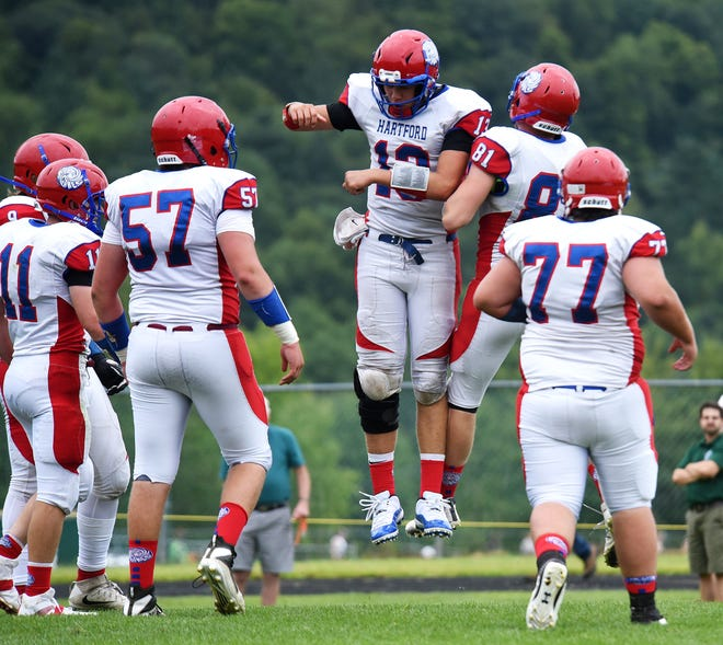 Hartford's Cole Jasmin, center, celebrates with Trevor Robbins during the Hurricanes' 35-33 win over defending champion St. Johnsbury in the Vermont high school football season opener at Fairbanks Field on Saturday.