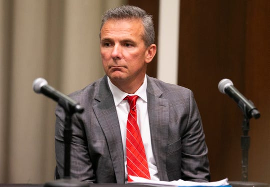 Ohio State Buckeyes head coach Urban Meyer listens as university president Michael Drake at Longaberger Alumni House speaks on the Ohio State University campus.