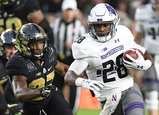Northwestern Wildcats running back Jeremy Larkin  (28) runs past against  Purdue Boilermaker safety Navon Mosley (27)  in the first half  at Ross-Ade Stadium.
