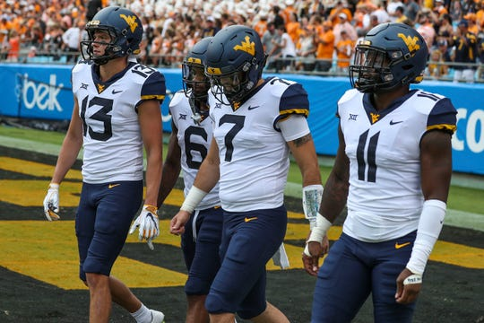 West Virginia Mountaineers wide receiver David Sills V (13), safety Dravon Askew-Henry (6), quarterback Will Grier (7), and linebacker David Long Jr. (11) walk to the coin toss before the game at Bank of America Stadium.