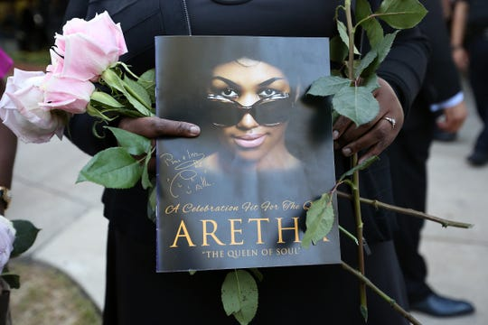 A mourner carries roses with a program from Aretha Franklin's funeral service at Greater Grace Temple in Detroit, on Friday, Aug. 31, 2018.