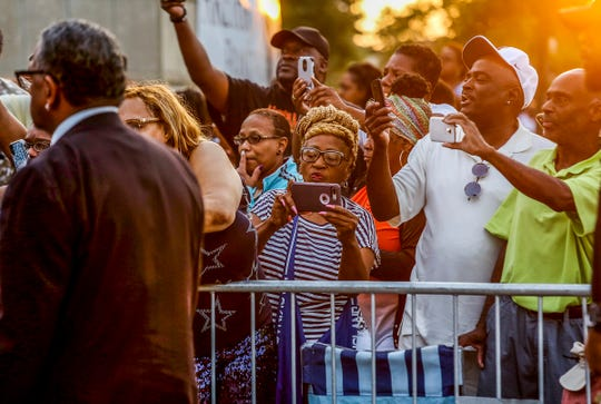 People crowd around to get a photograph as Aretha Franklin's casket arrives at the Charles H. Wright Museum of African American History in Detroit on Tuesday, Aug. 28, 2018.