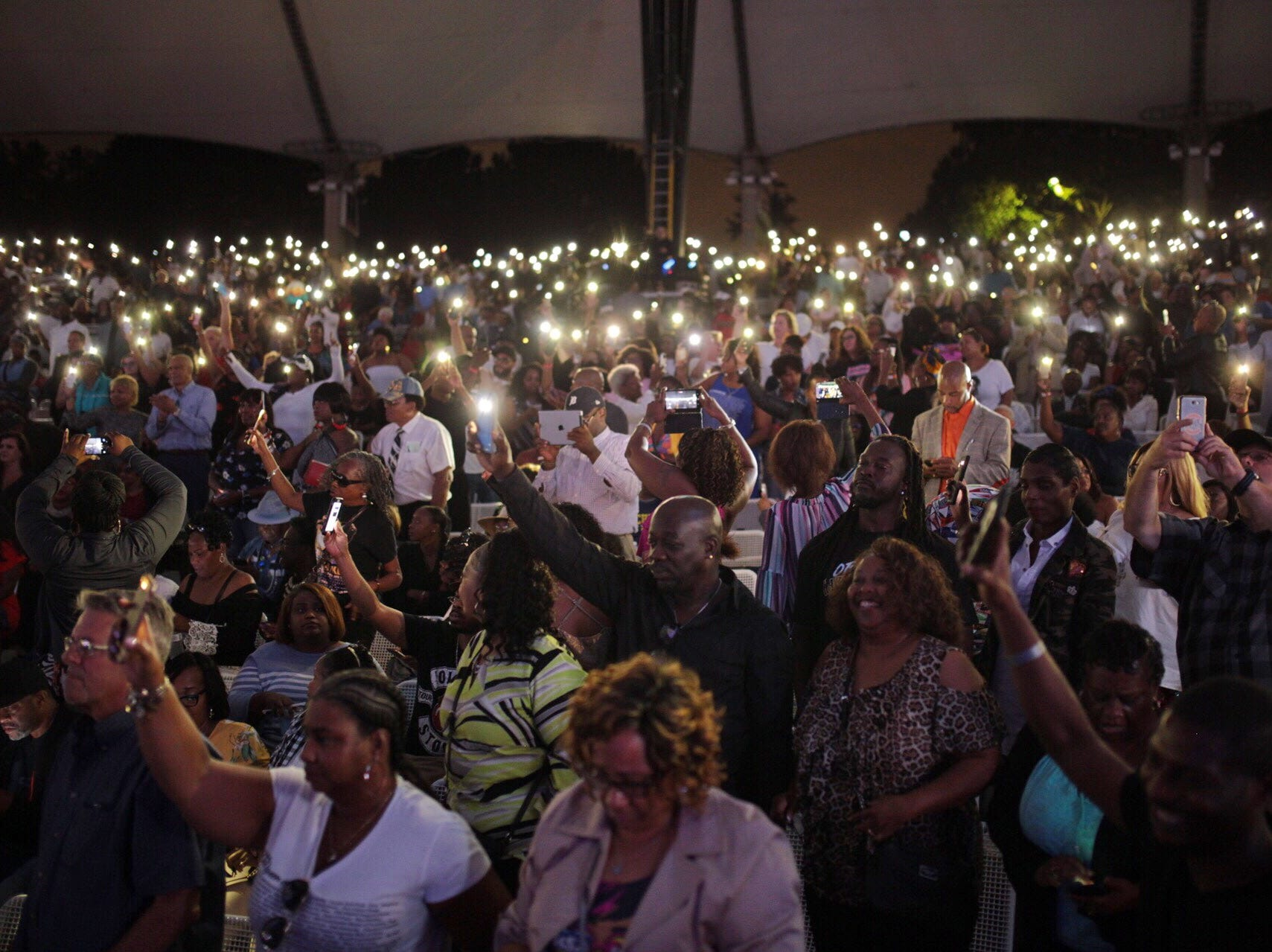 People hold their phones up during an Aretha Franklin tribute concert at Chene Park Amphitheatre in Detroit on Thursday, August 30, 2018.