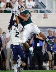 Michigan State's Cody White catches a pass in the end zone against Utah State's Ja'Marcus Ingram in the fourth quarter Aug. 31, 2018, in East Lansing. The play was called back due to a penalty.