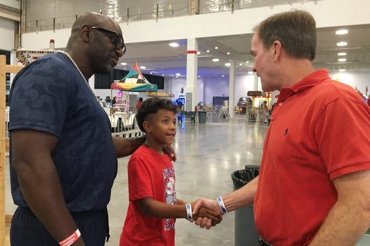 Eric Triplett and his 10-year-old son Donovan, both of Walled Lake, speak with Republican candidate for governor Bill Schuette during the Michigan State Fair at the Suburban Collection Showplace in Novi on Monday, September 3, 2018.
