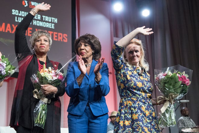 Left to right, Congresswoman Brenda Lawrence (D-MI), left, Congresswoman Maxine Waters (D-CA), and Congresswoman Debbie Dingell (D-MI), wave at the attendees at the Sojourner Truth Lunch of the Women's Convention at Cobo Center in downtown Detroit, Saturday, October 28, 2017.