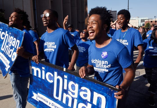 l-r, Dwight Bailey, 18, (sunglasses on), and Aaron Cooper, 19, of Michigan United organization walks the parade route along Michigan Ave. to Hart Plaza.