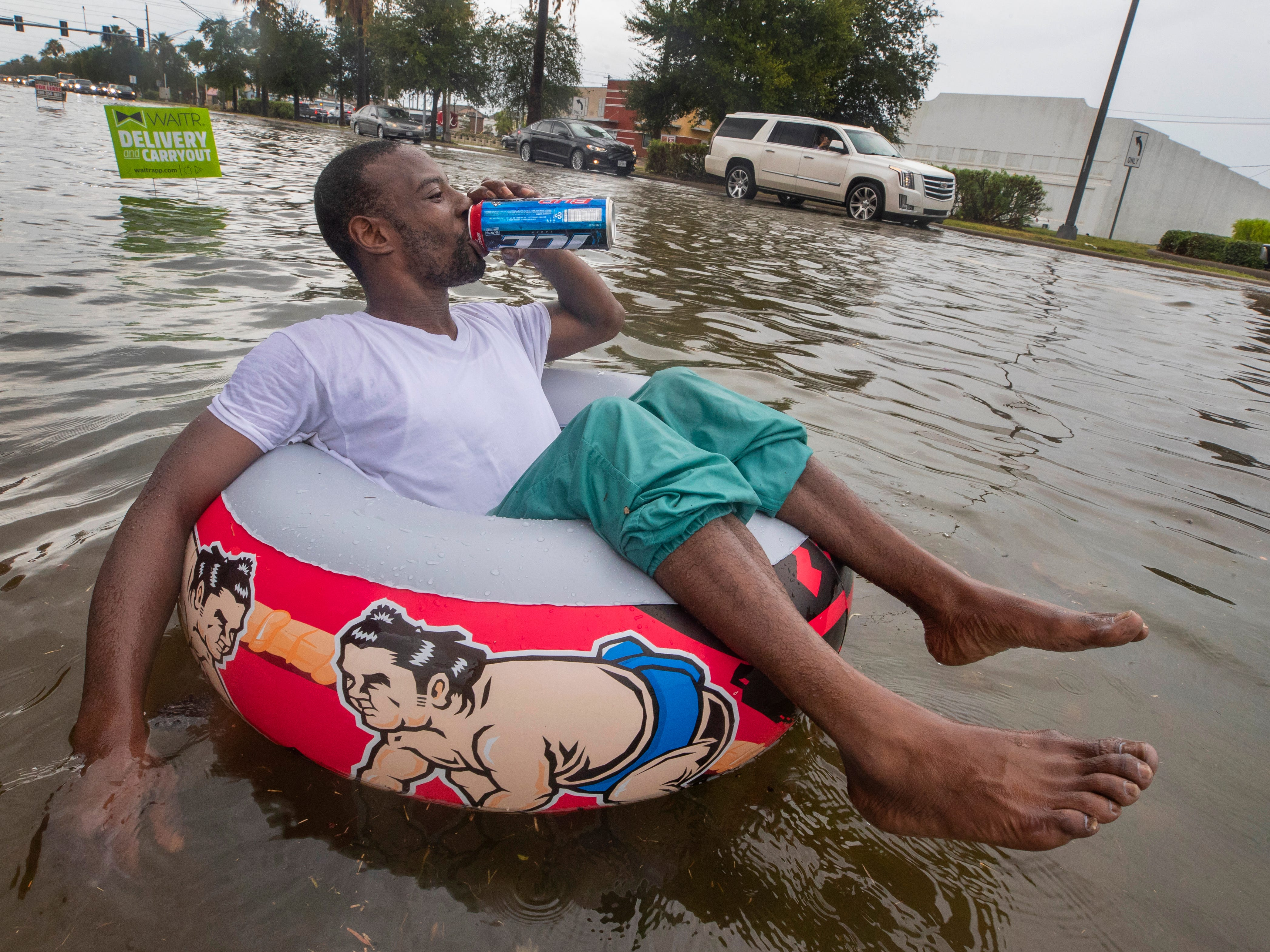 Johnny Jones drinks a beer while floating and watching a single-file line of drivers make their way down Broadway Boulevard after heavy rains caused substantial street flooding in Galveston, Texas, on Monday, Sept. 3, 2018.