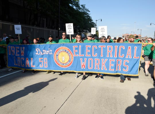 IBEW Local 58 electrical workers walk the parade route in 2018 along Michigan Ave. to Hart Plaza. Federal prosecutors have released text messages between an IBEW official and state Rep. Larry Inman about his vote on an initiative to repeal Michigan's prevailing wage law.