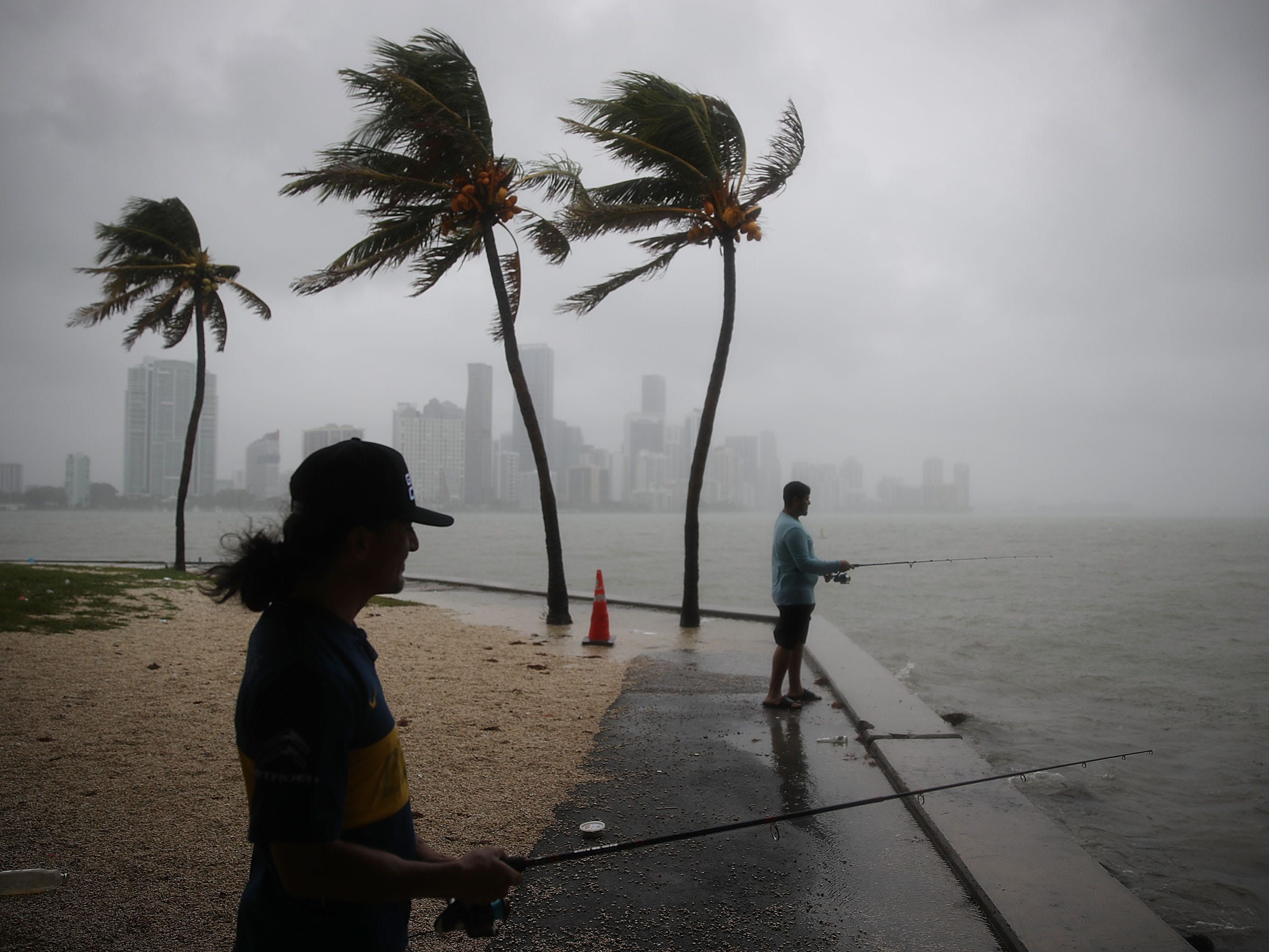 Walter Augier,  left, and Jhon M. fish as rain and wind are whipped up by Tropical Storm Gordon on Monday, September 3, 2018, in Miami, Florida.