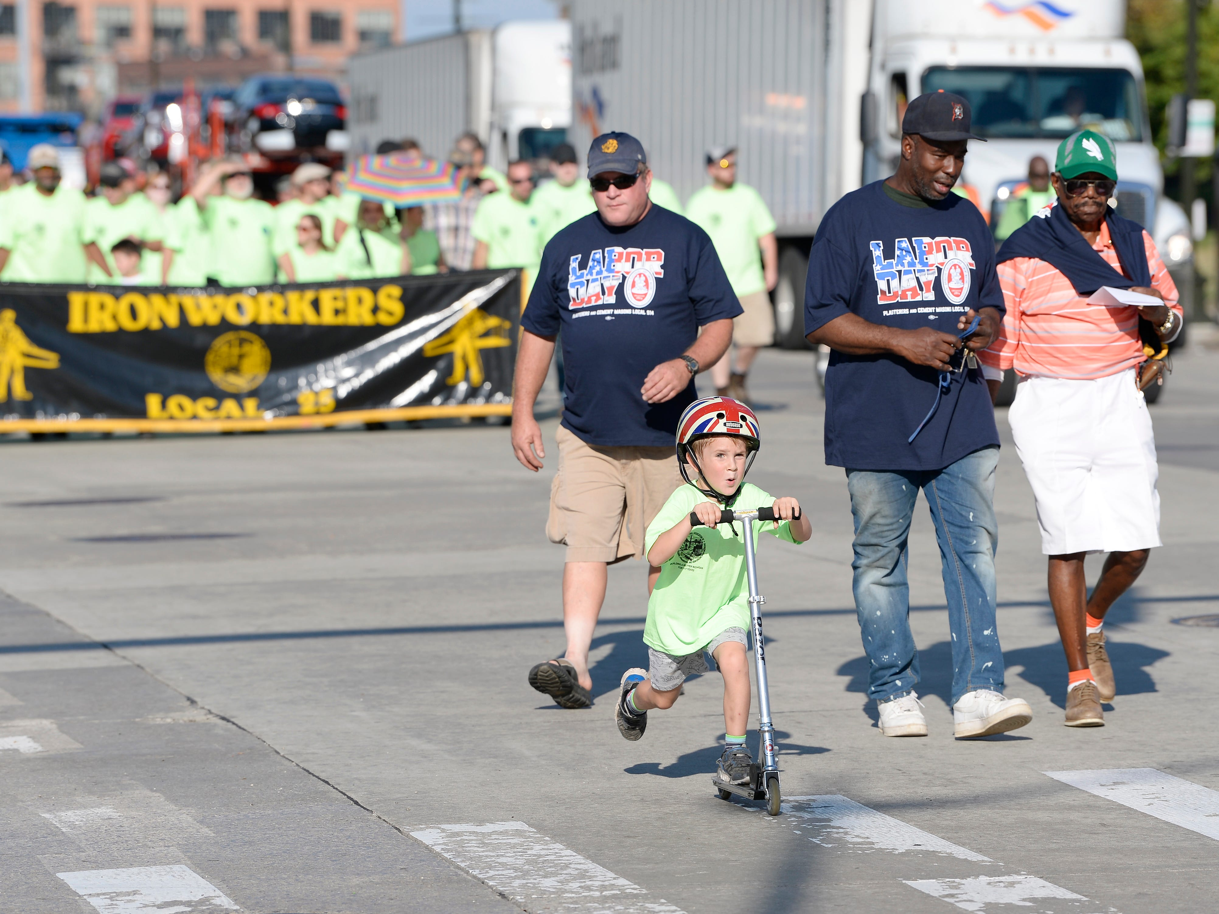 Jack Lobley, 5, of Detroit rides his scooter on the parade route.
