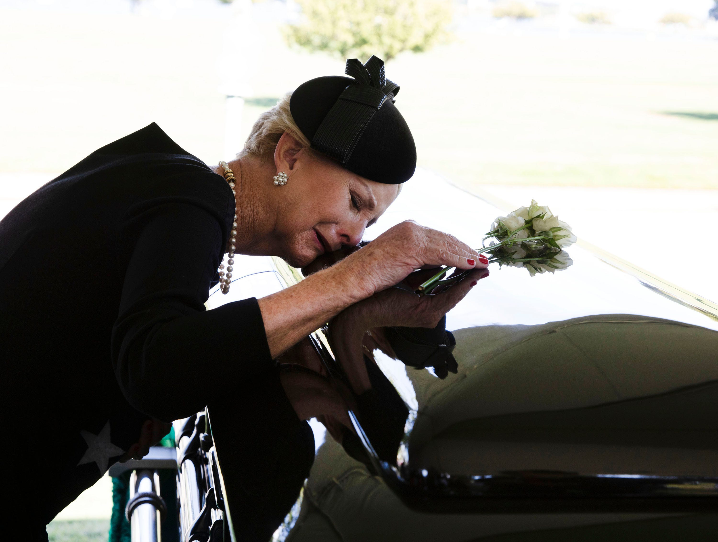 Cindy McCain lays her head on the casket of Sen. John McCain, R-Ariz., during a burial service at the cemetery at the United States Naval Academy in Annapolis, Md., on Sunday, Sept. 2, 2018.