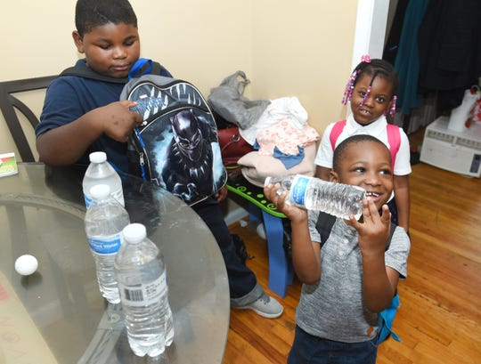 Adrian Nealy, left, gets his books and bottled water ready for school with his brother Rico, 3, and sister Cassidy, 4.  Detroit Public Schools Community District has alerted parents that only bottled water is available in the district until further notice.