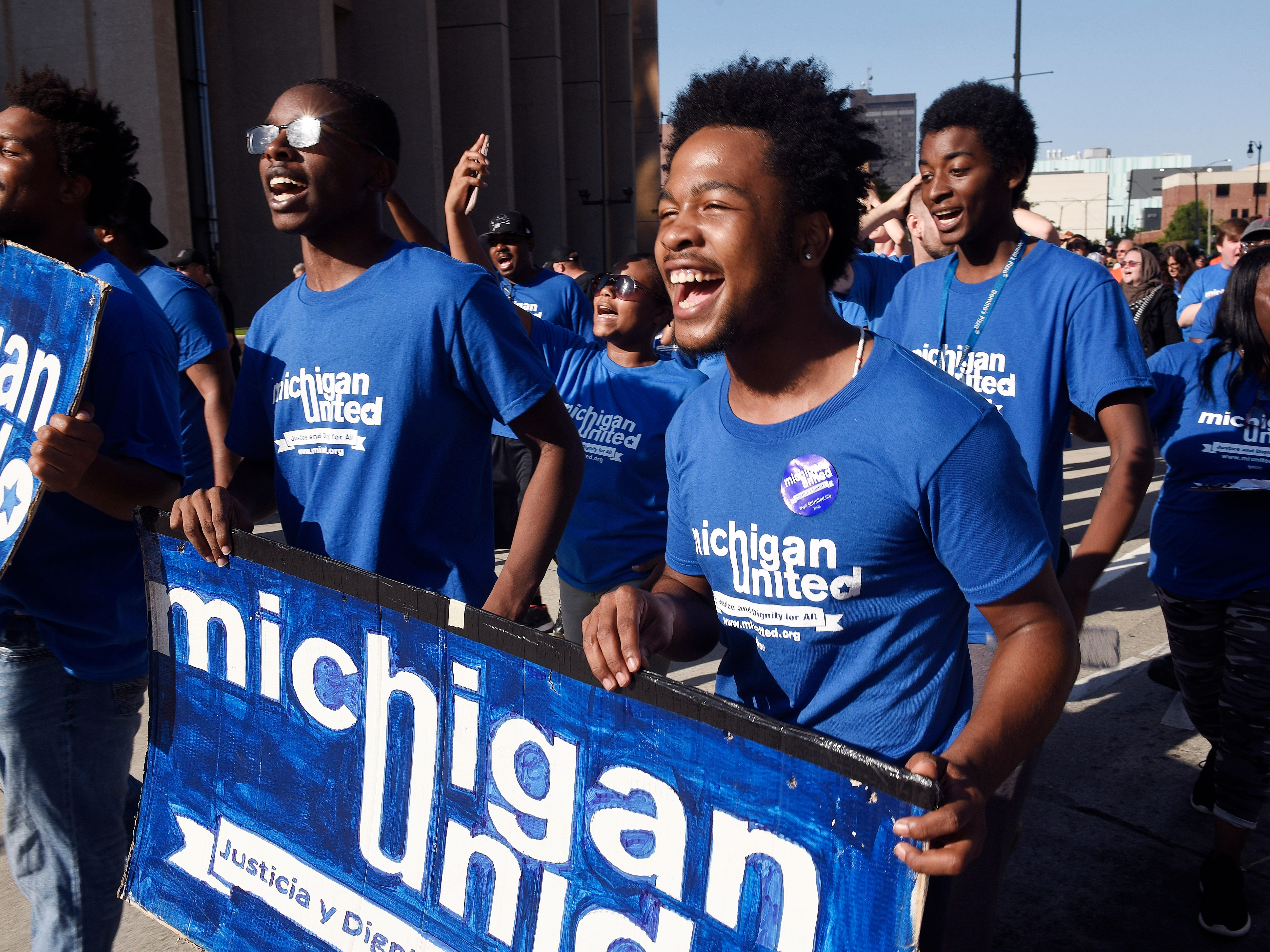Dwight Bailey, 18, center, and Aaron Cooper, 19, right, of Michigan United walk the parade route along Michigan Ave. to Hart Plaza.