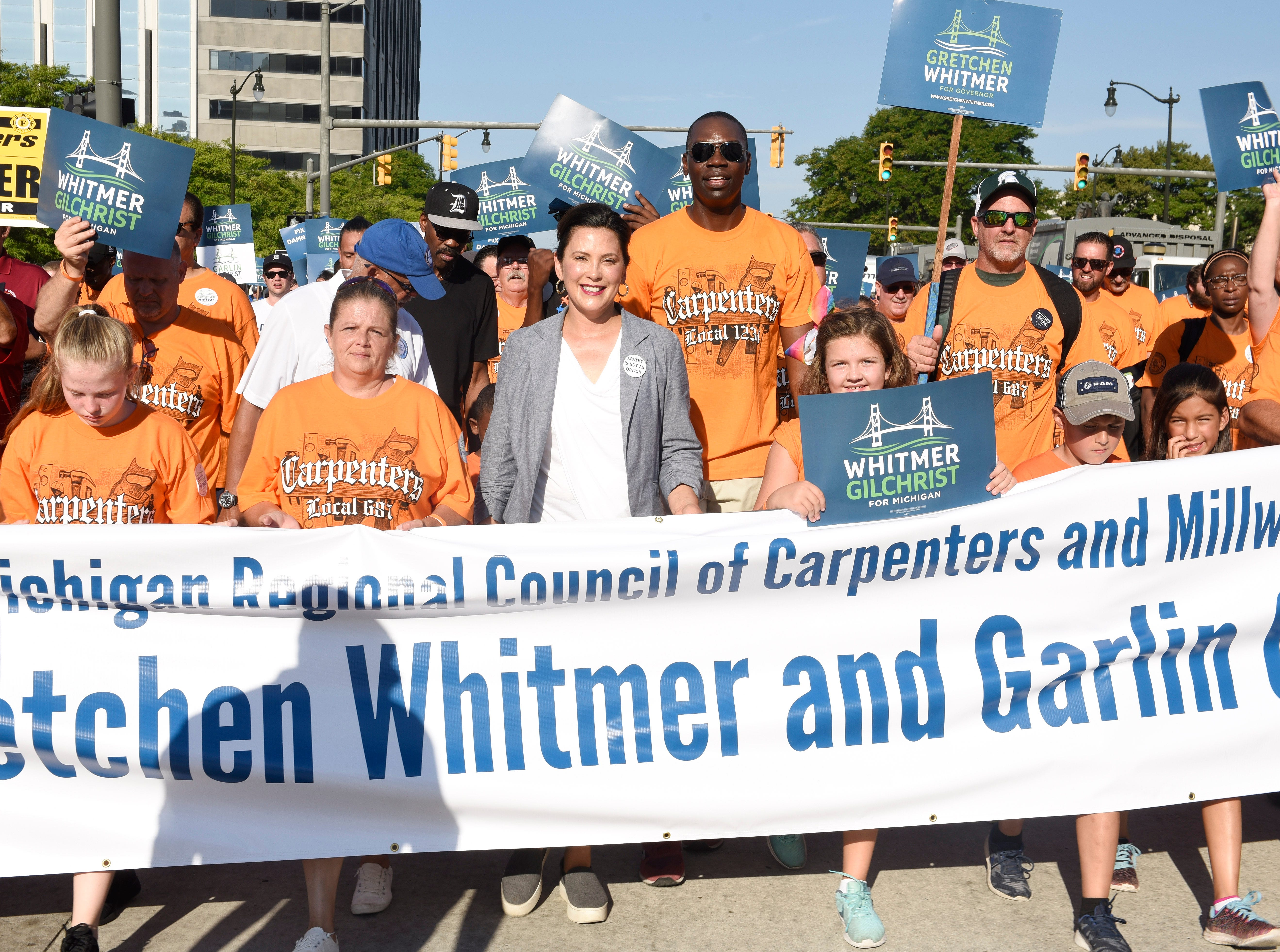 Democratic nominee for governor Gretchen Whitmer, center, walks the parade route with the Michigan Regional Council of Carpenters and Millwrights.
